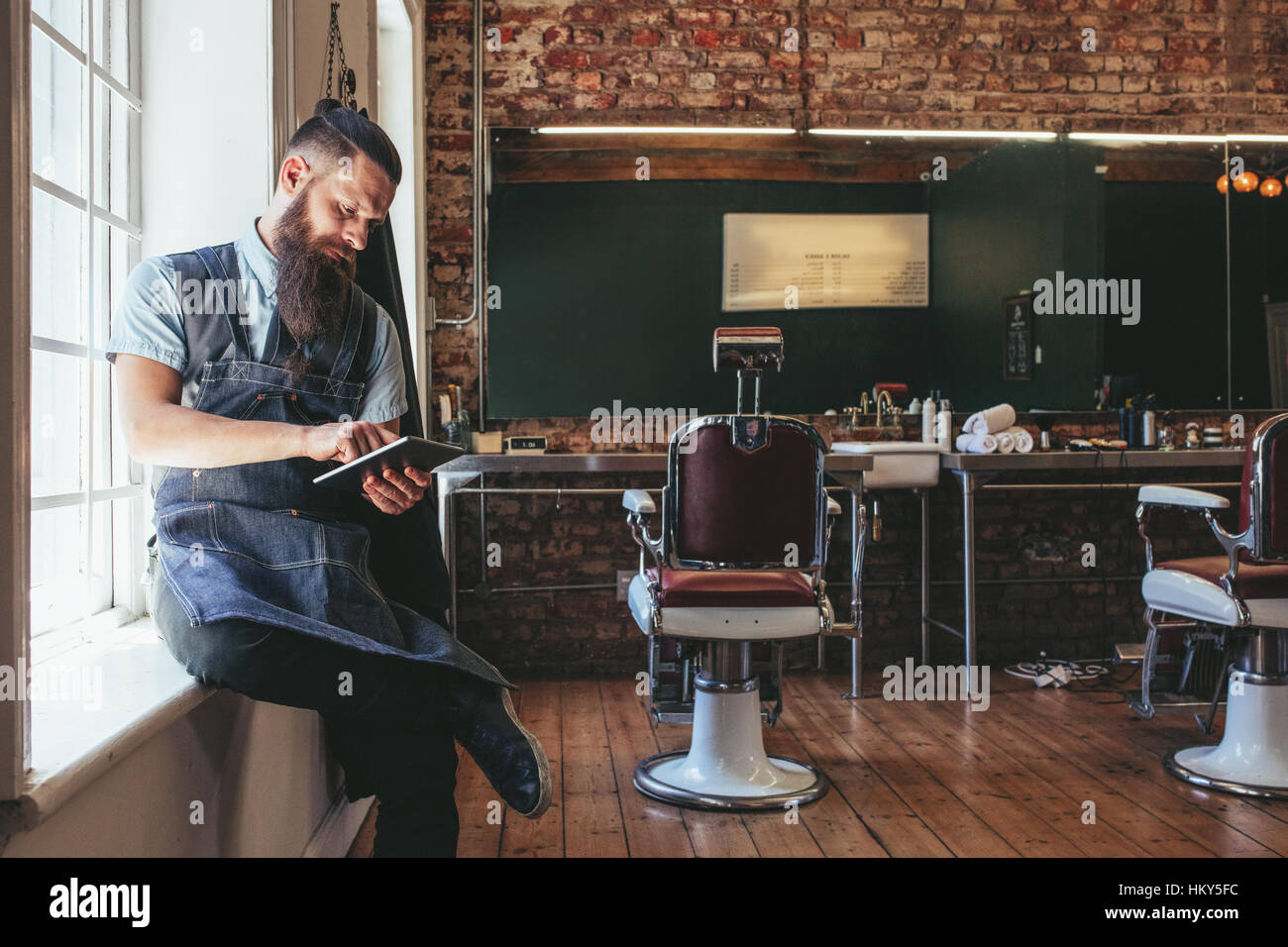 Barber with digital tablet sitting on window sill of salon. Hairdresser organizing his business using latest technology. - Stock Image