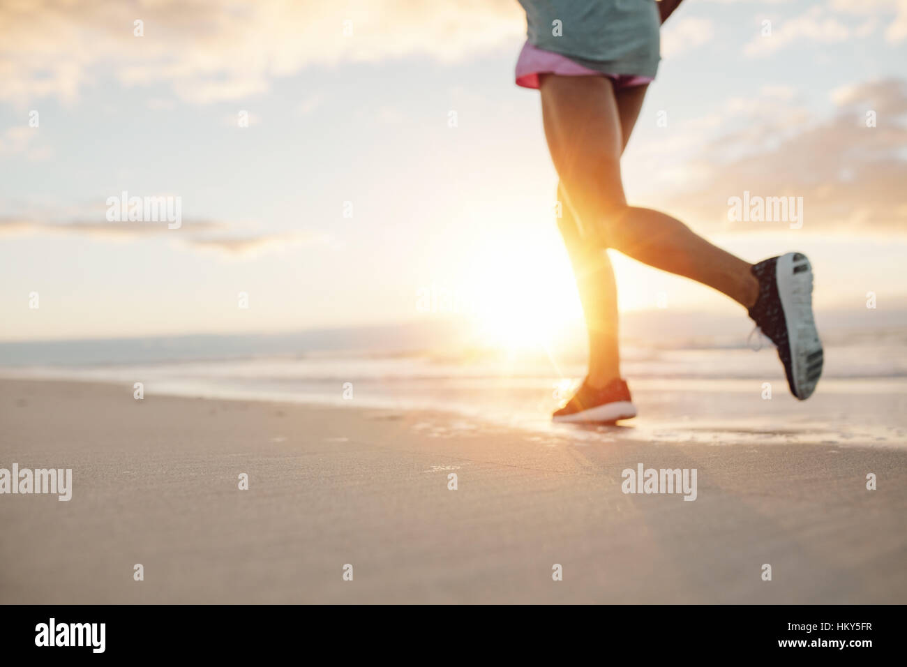 Feet of young woman jogging on the beach. Fitness female on morning run at sea shore. - Stock Image