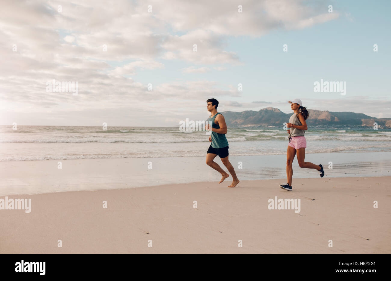 Full length shot of fit young man and woman running on the beach. Couple of runners on the sea shore. - Stock Image