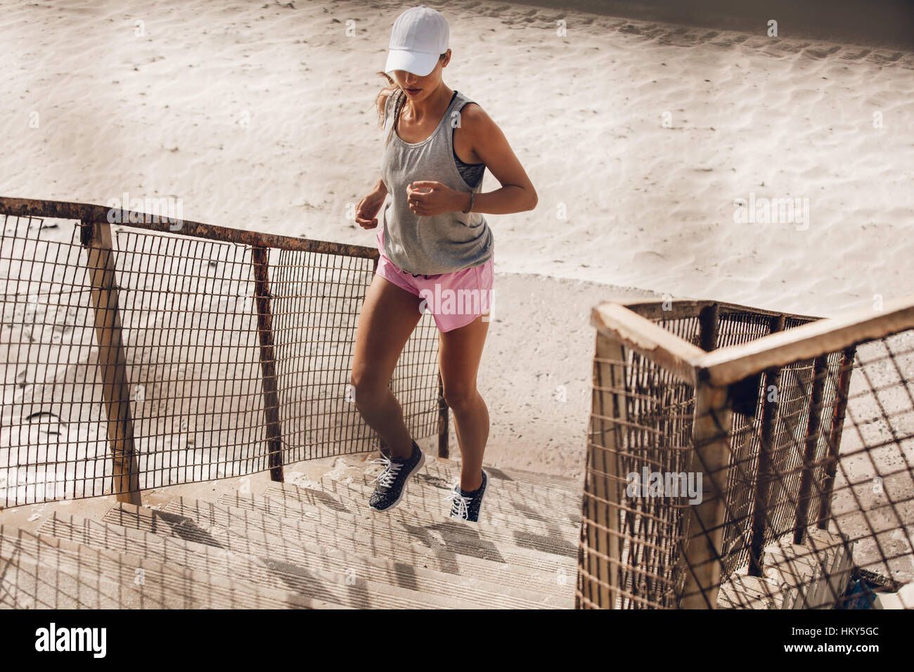 Fit young woman running up the staircase on beach. Young female runner working out on steps on sea shore. - Stock Image
