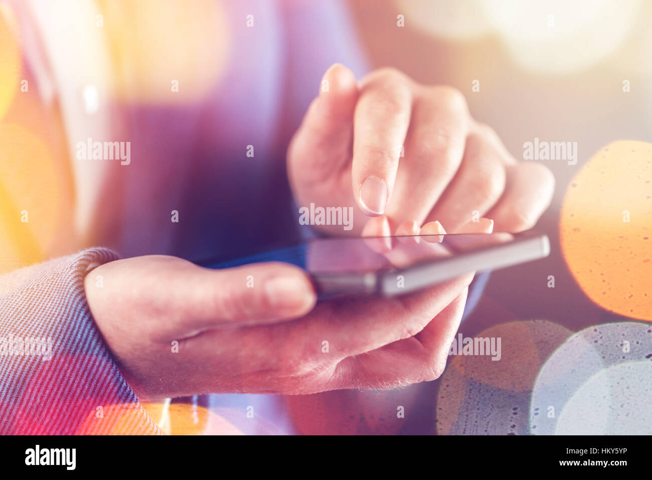 Female hands with mobile phone, finger on touchscreen - Stock Image