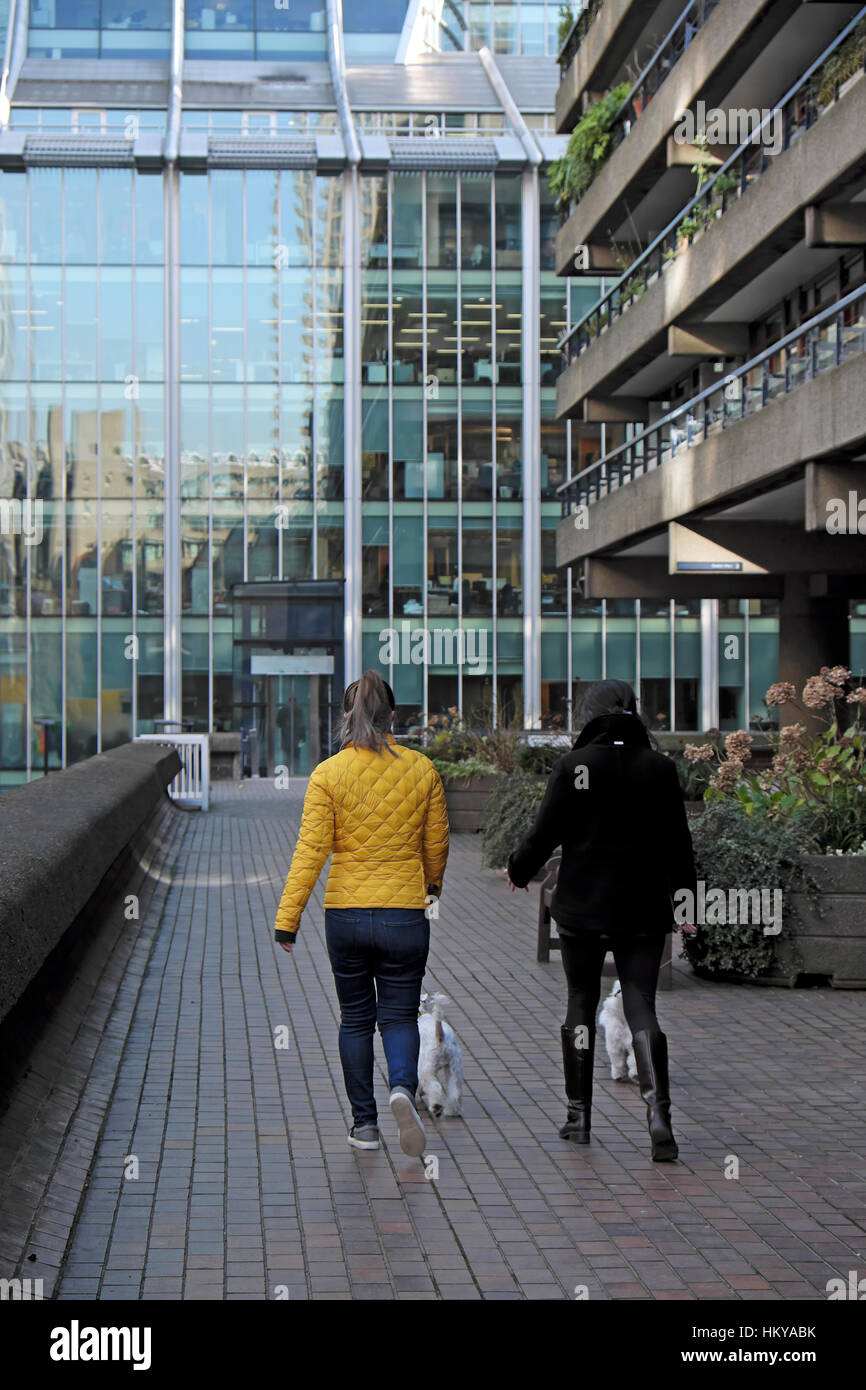 Two women walking dogs outside office buildings at the Barbican in the City of London, UK  KATHY DEWITT - Stock Image