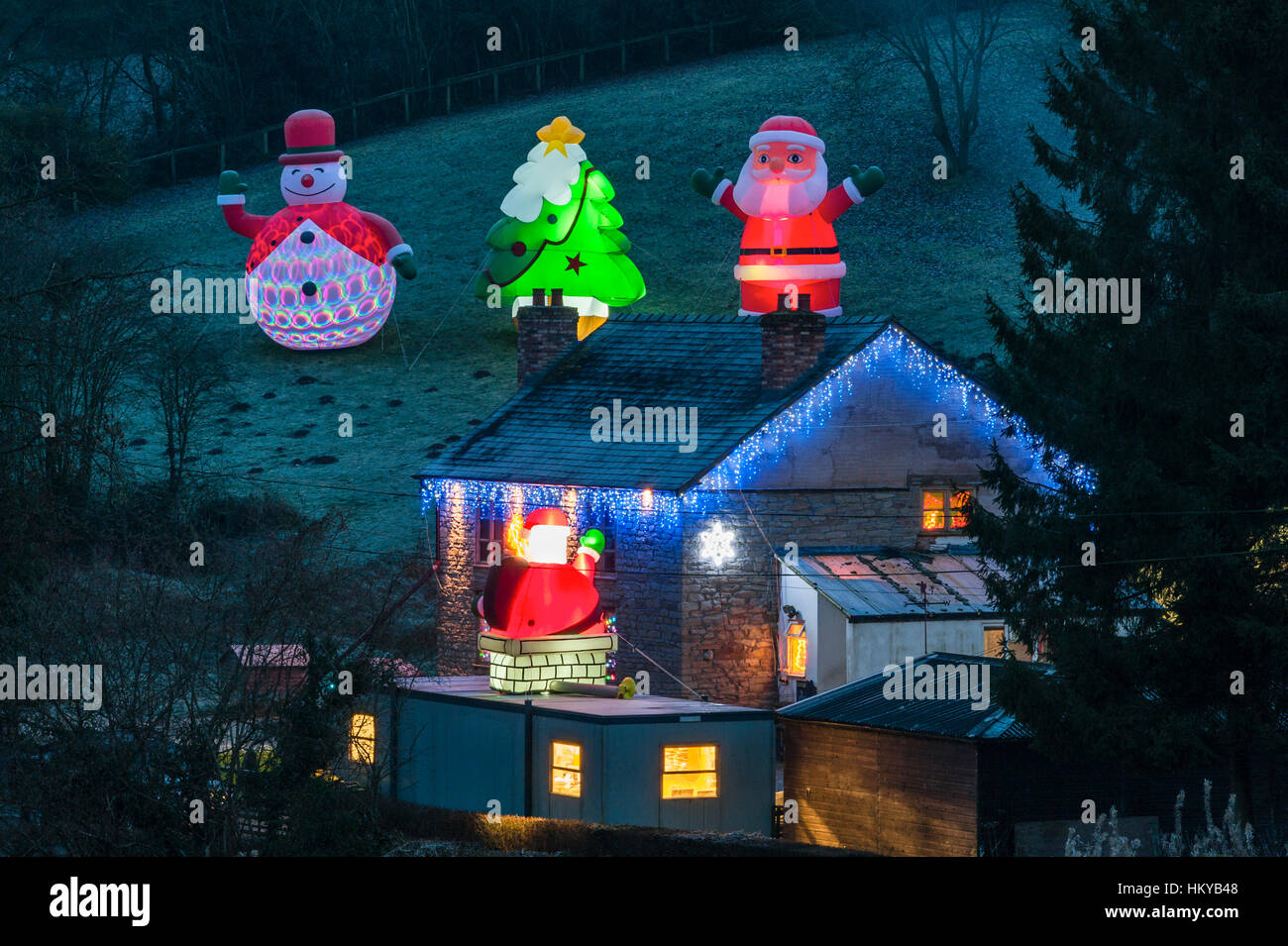 Huge illuminated inflatable Christmas figures surround a remote cottage at night in rural Herefordshire, UK. - Stock Image