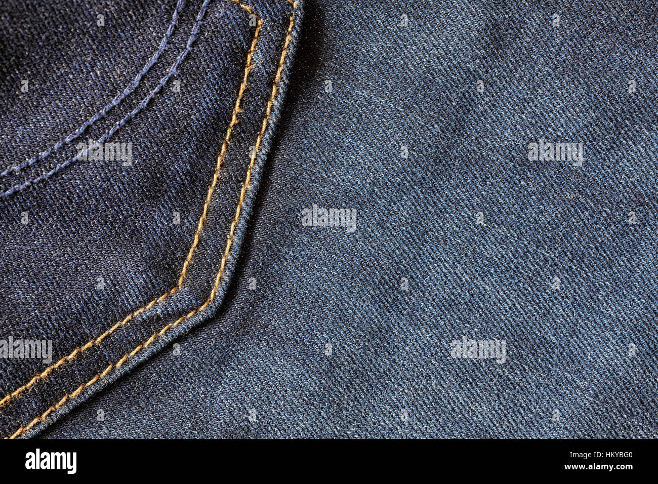 Close up picture of blue jeans fabric with stitches, selective focus, background or texture. - Stock Image