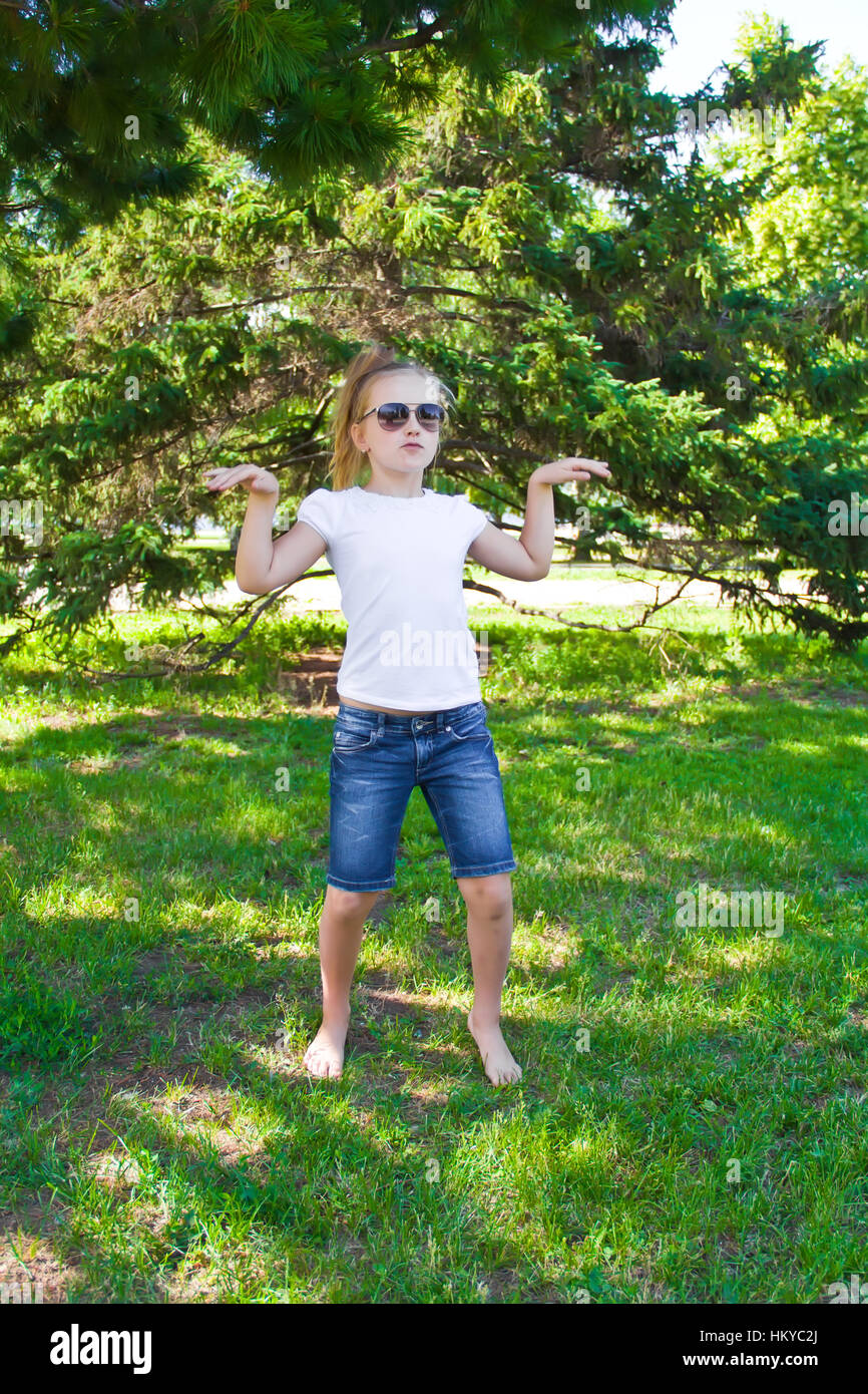 Photo of cute dancing girl with sunglass in summer - Stock Image