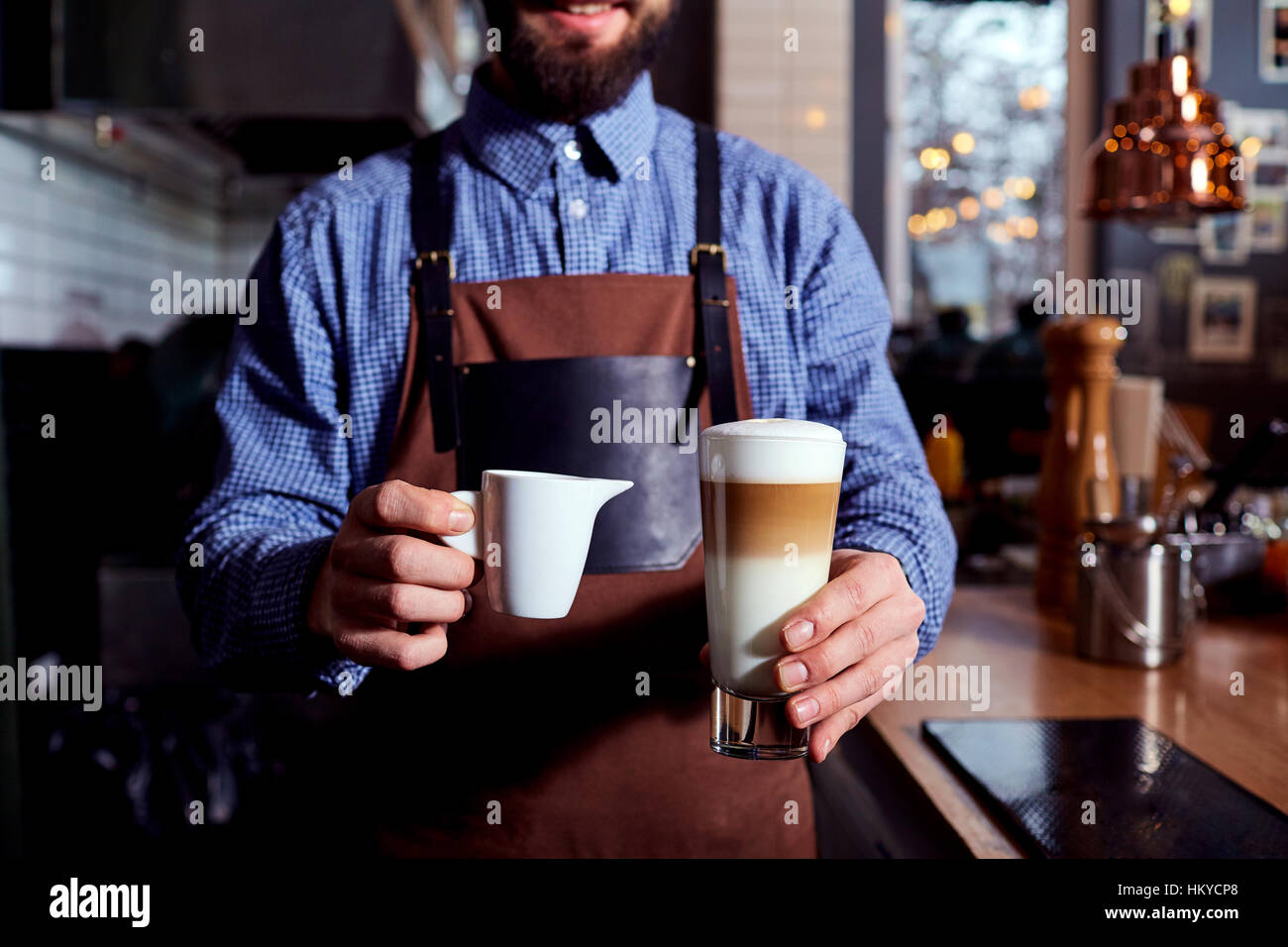 Barista bartender with a cappuccino in hand - Stock Image