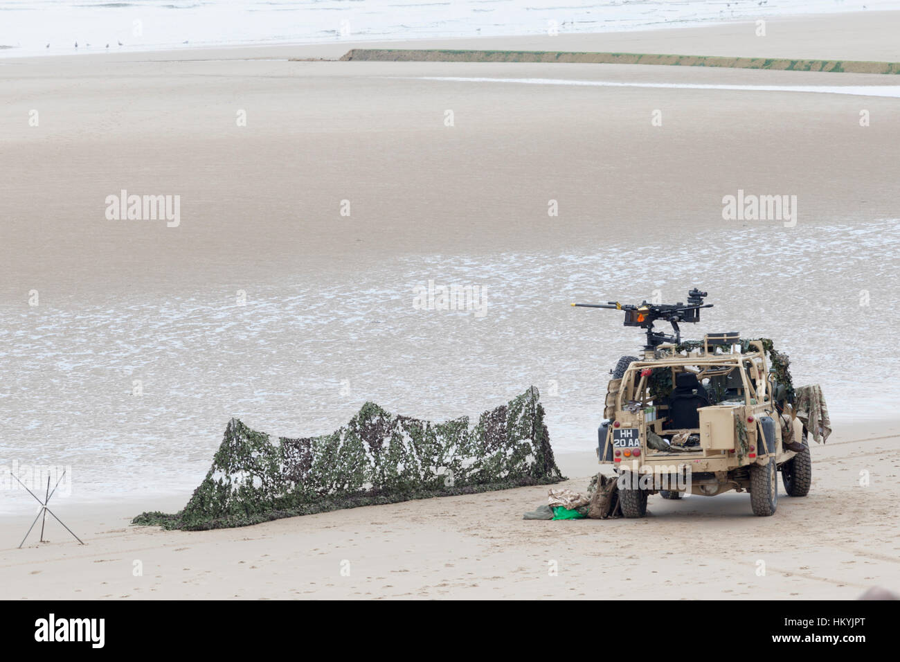 British Army Land Rover parked on a beach with a machine gun mounted on it & camouflage netting nearby during - Stock Image