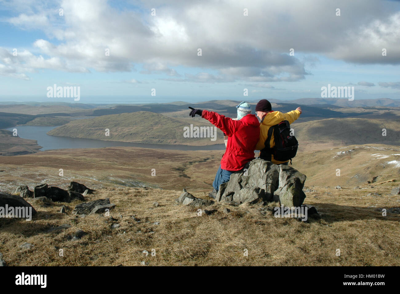 Two hill walkers sitting on rocks at summit reading map and pointing in opposite directions, bright winters day - Stock Image