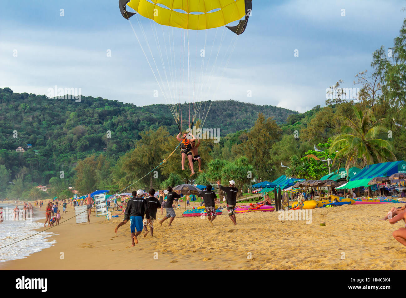 Parachutists landing on the beach insures assistants crowd in black Stock Photo