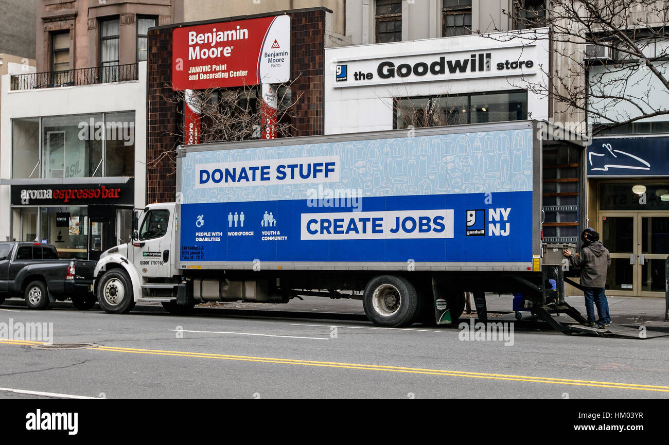 Two employees are unloading a Goodwill truck is parked in front of their store. - Stock Image