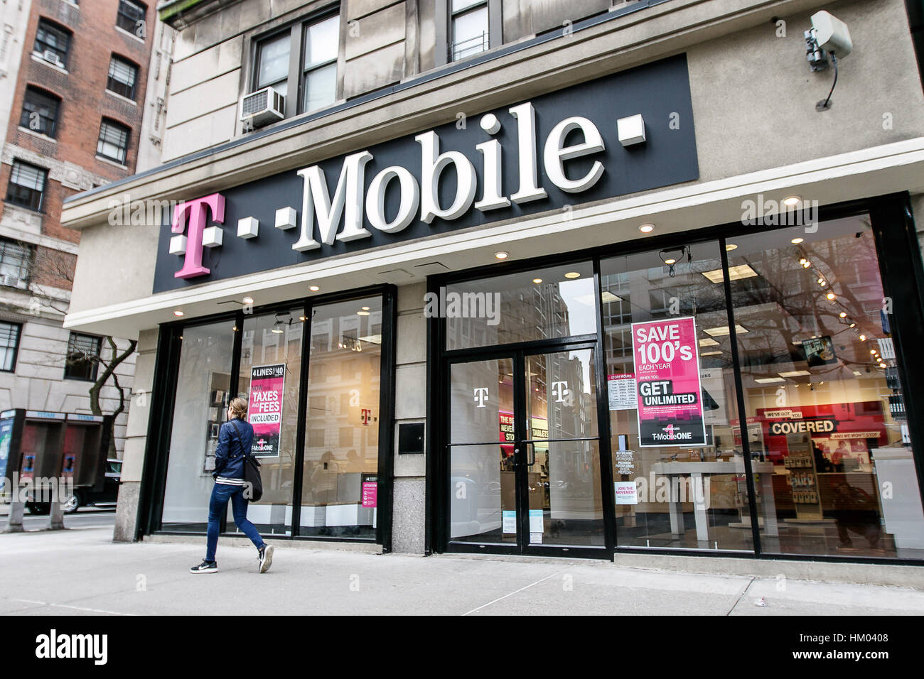 A Woman Is Walking By A T Mobile Store In Manhattan Stock Photo