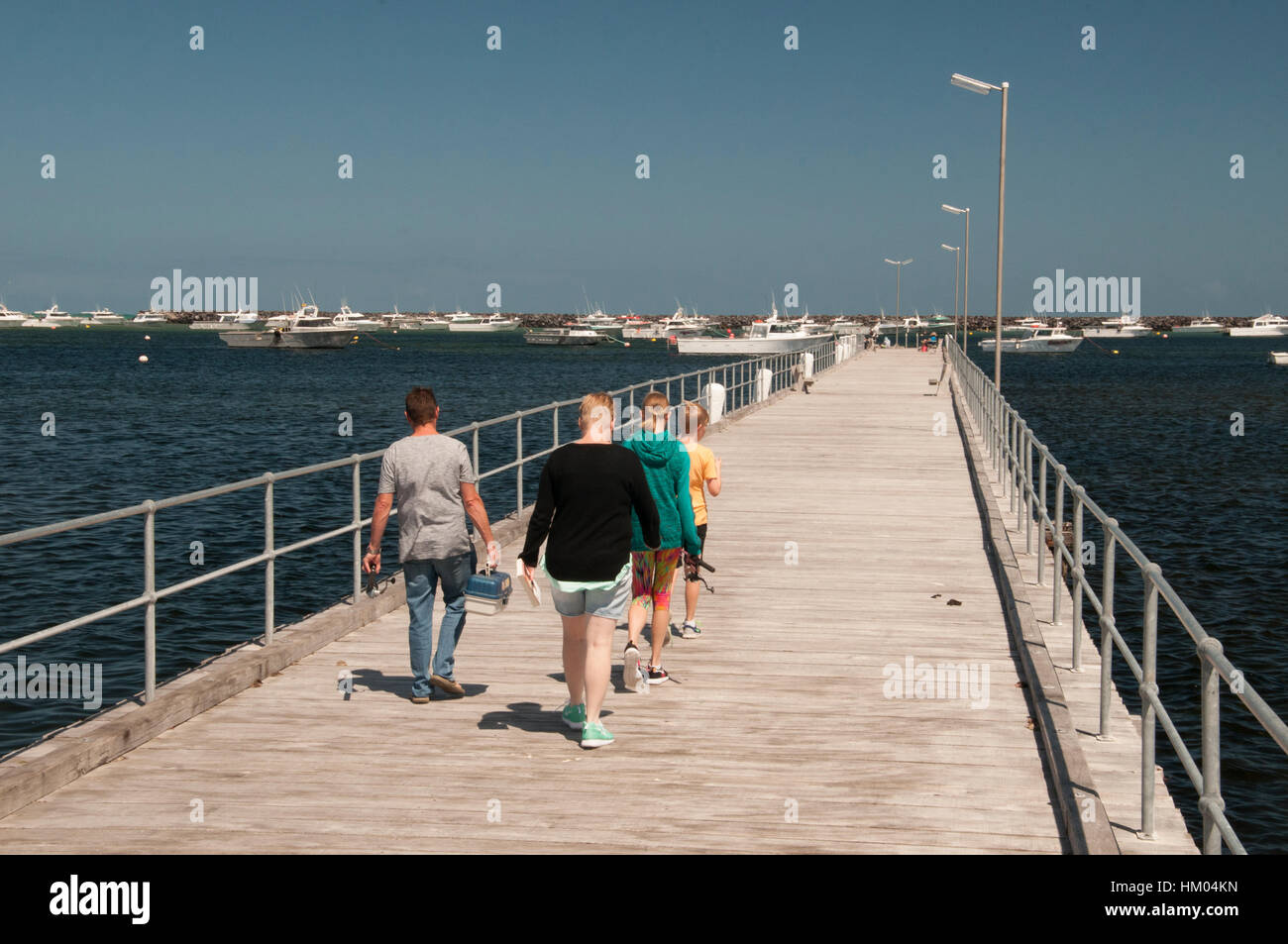 Walking along the pier at the historic fishing town of Port MacDonnell, southeast South Australia - Stock Image