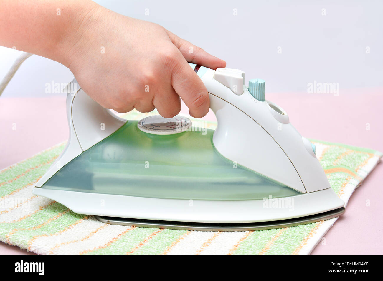 Iron in the hand. Ironing - Stock Image