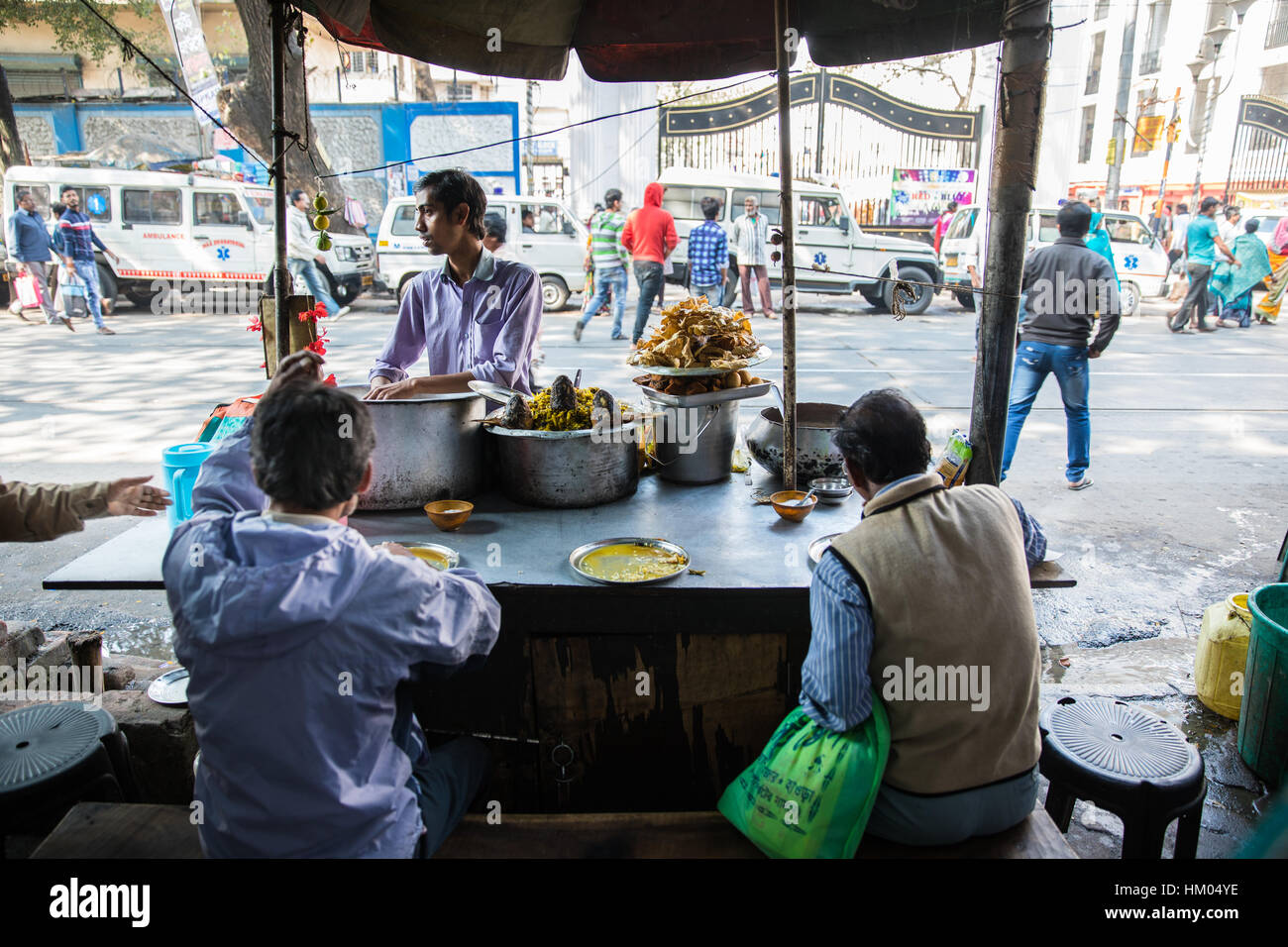 People eating lunch at a street food stall in Kolkata (Calcutta), West Bengal, India. - Stock Image
