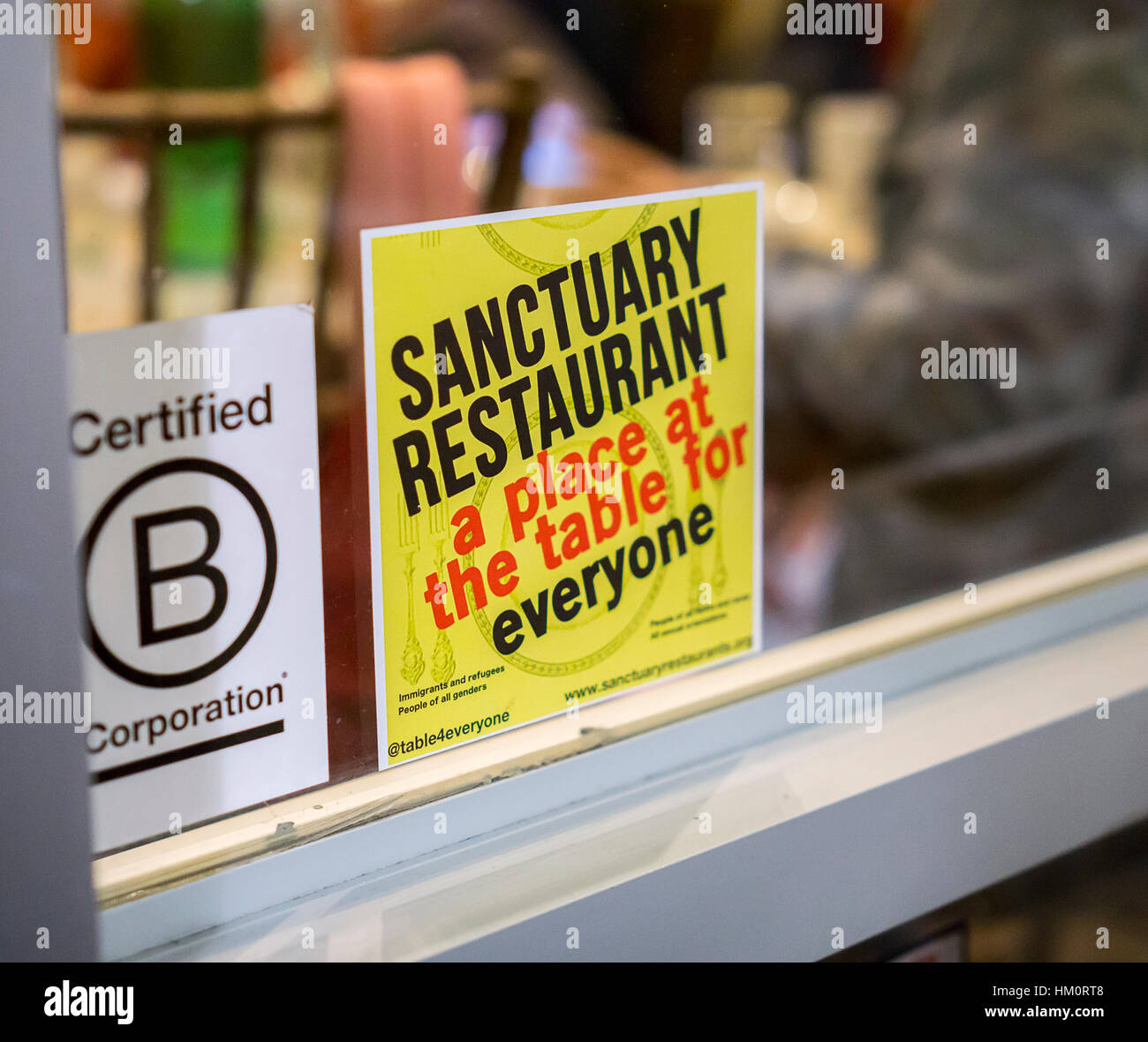 A sign in the window of the Green Table restaurant in Chelsea in New York announces that it is a 'sanctuary - Stock Image