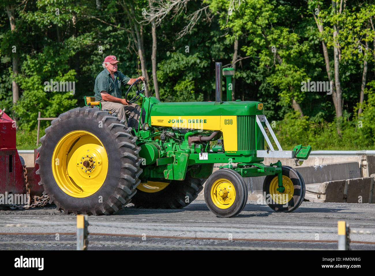 A farmer drives his John Deere model 630 tractor in the