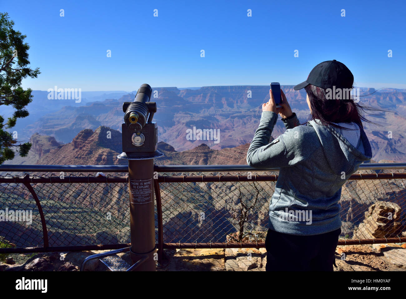Woman with cellphone taking photo Grand Canyon National Park South Rim at Desert View Watchtower visitors viewpoint - Stock Image