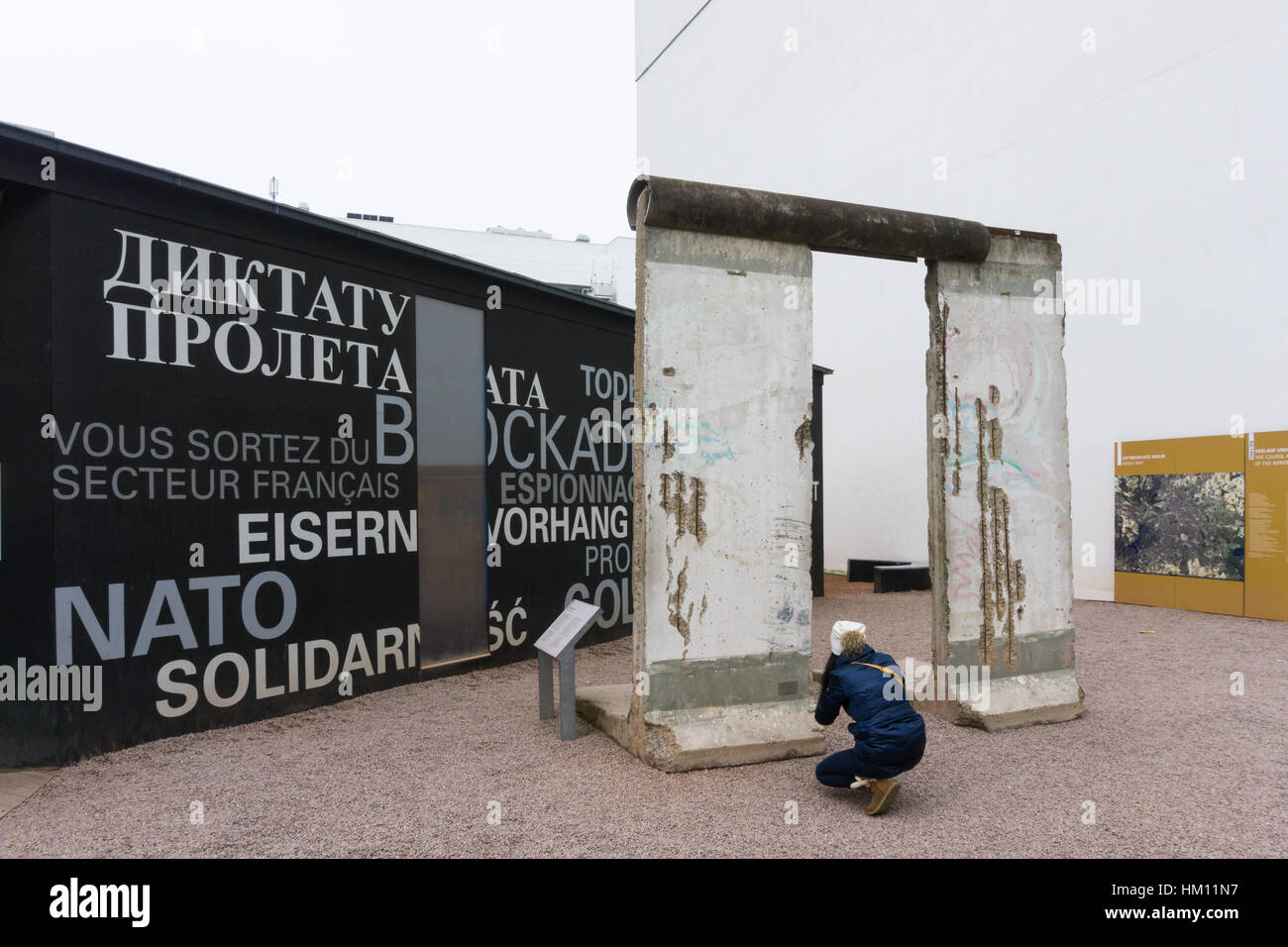 A woman takes a photo of a section of the berlin wall at the BlackBox Kalter Krieg exhibition - Stock Image