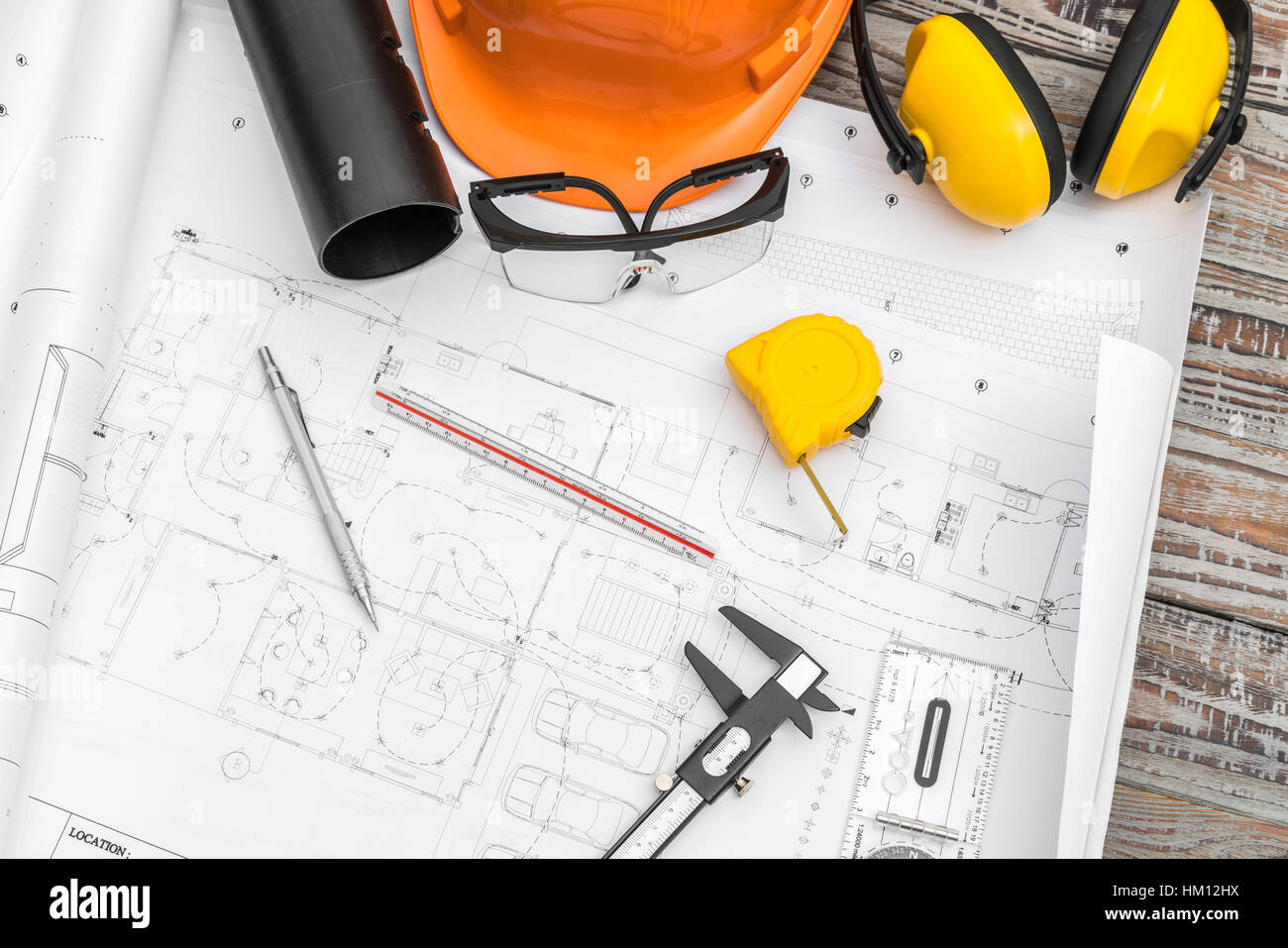 drawing tools. Construction Plans With Helmet And Drawing Tools On Blueprints