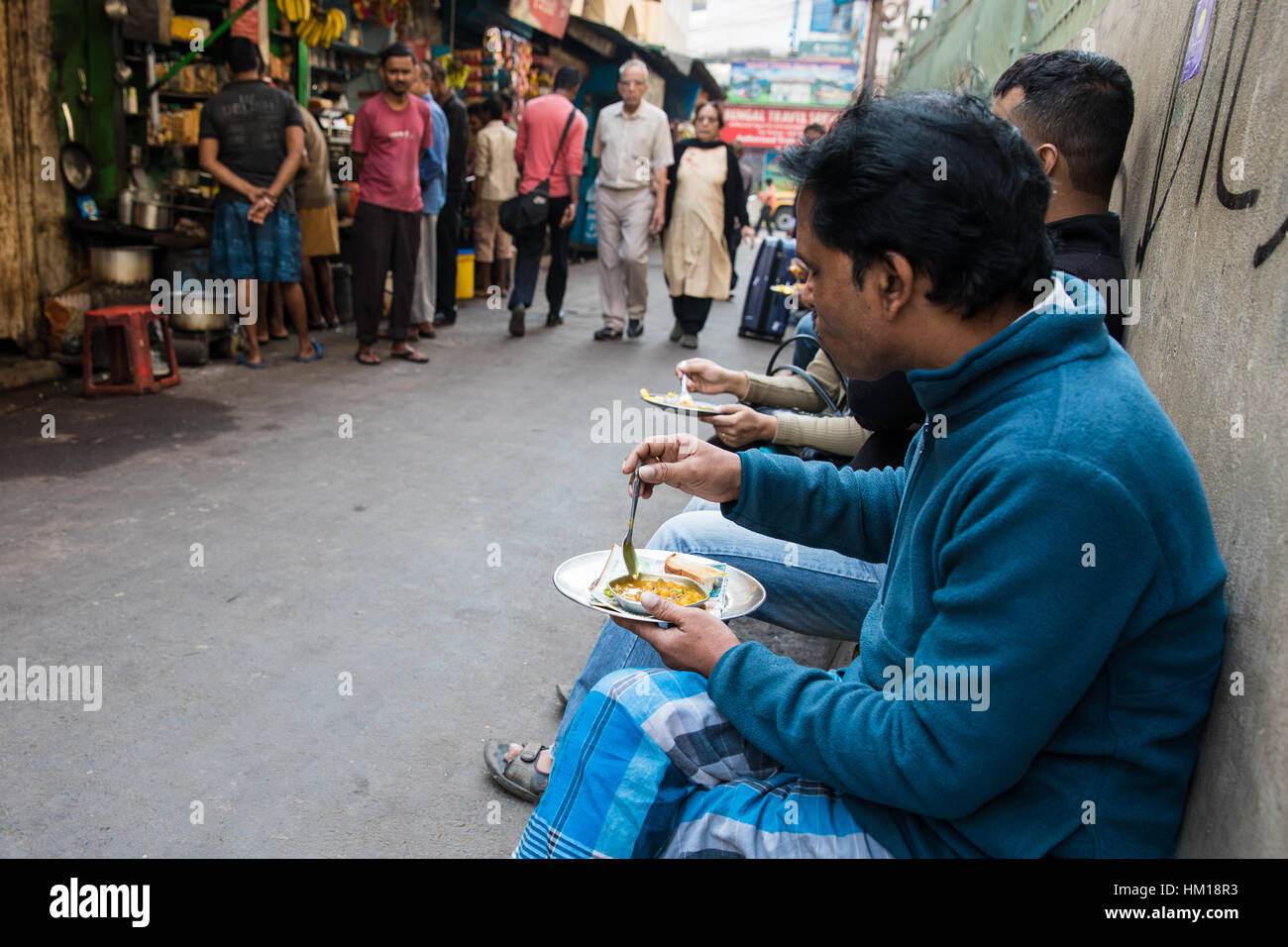 A mean eats breakfast from a street stall on Hertford Lane in Kolkata (Calcutta), West Bengal, India. - Stock Image