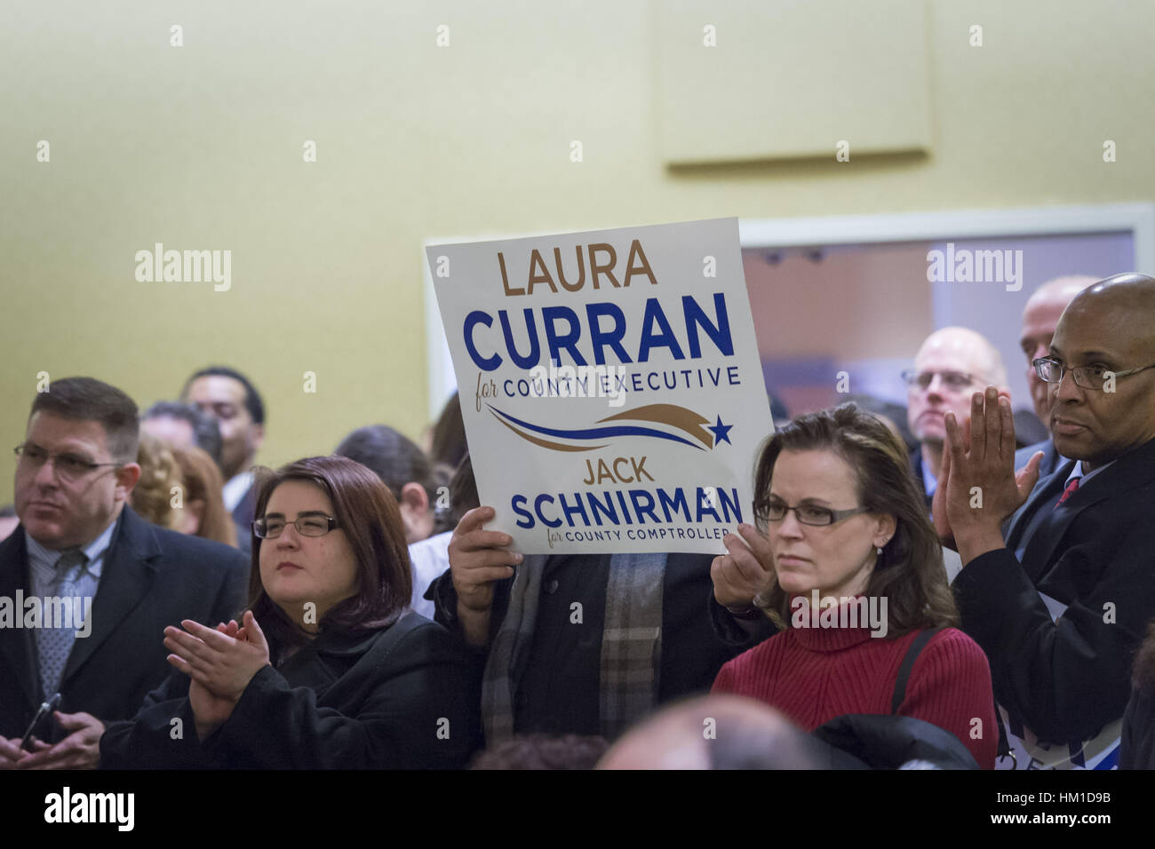 Uniondale, USA. 30th Jan, 2017. Audience members clap and hold up signs supporting Laura Curran, candidate for Nassau - Stock Image
