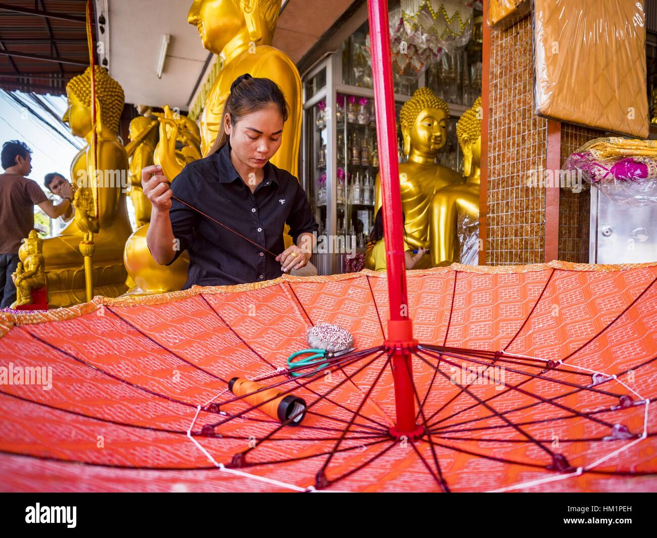 Bangkok, Thailand. 1st Feb, 2017. A woman works on a large traditional parasol at a shop that makes and sells Buddhist - Stock Image