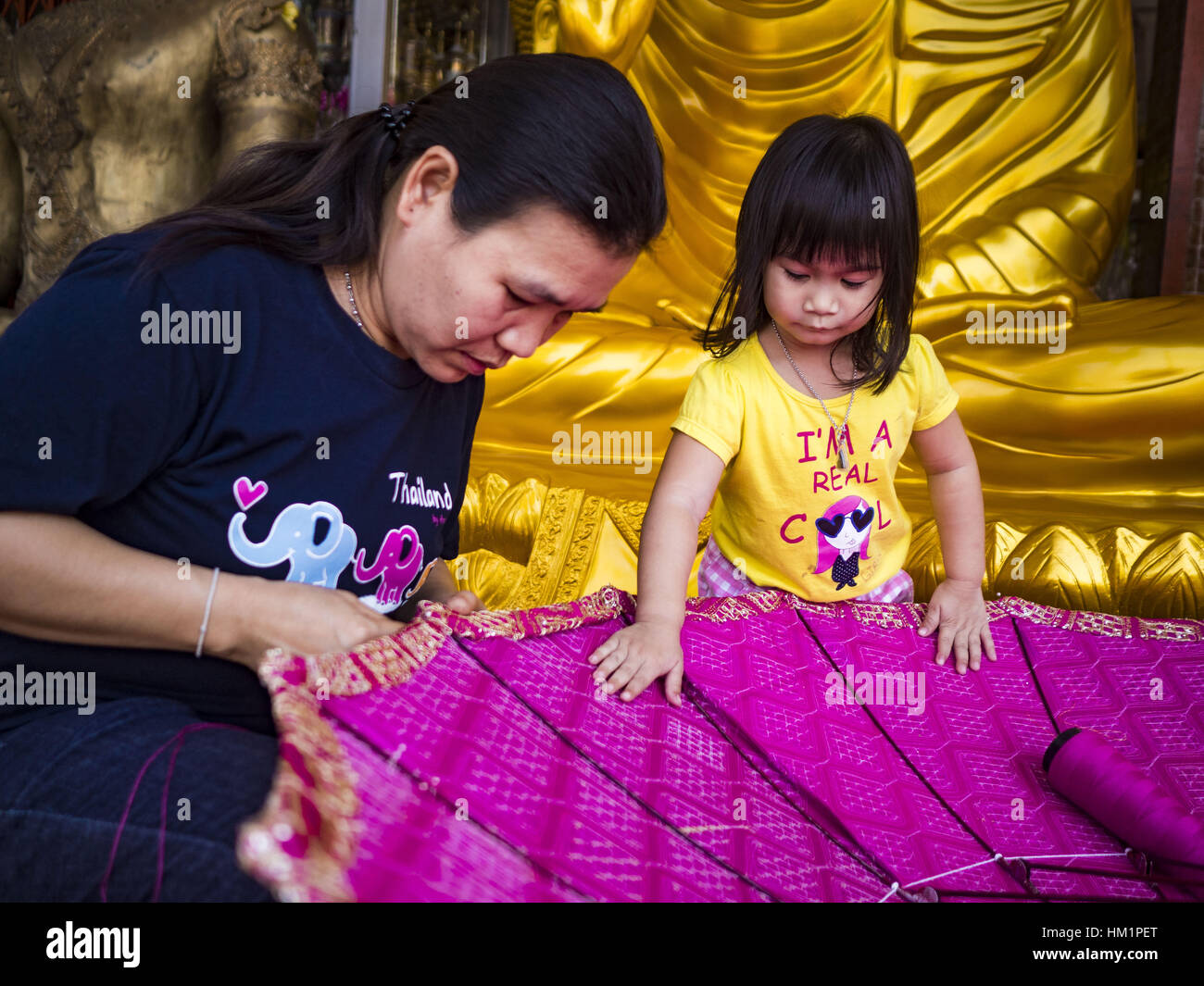 Bangkok, Thailand. 1st Feb, 2017. A girl and her mother work on a large traditional parasol at a shop that makes - Stock Image