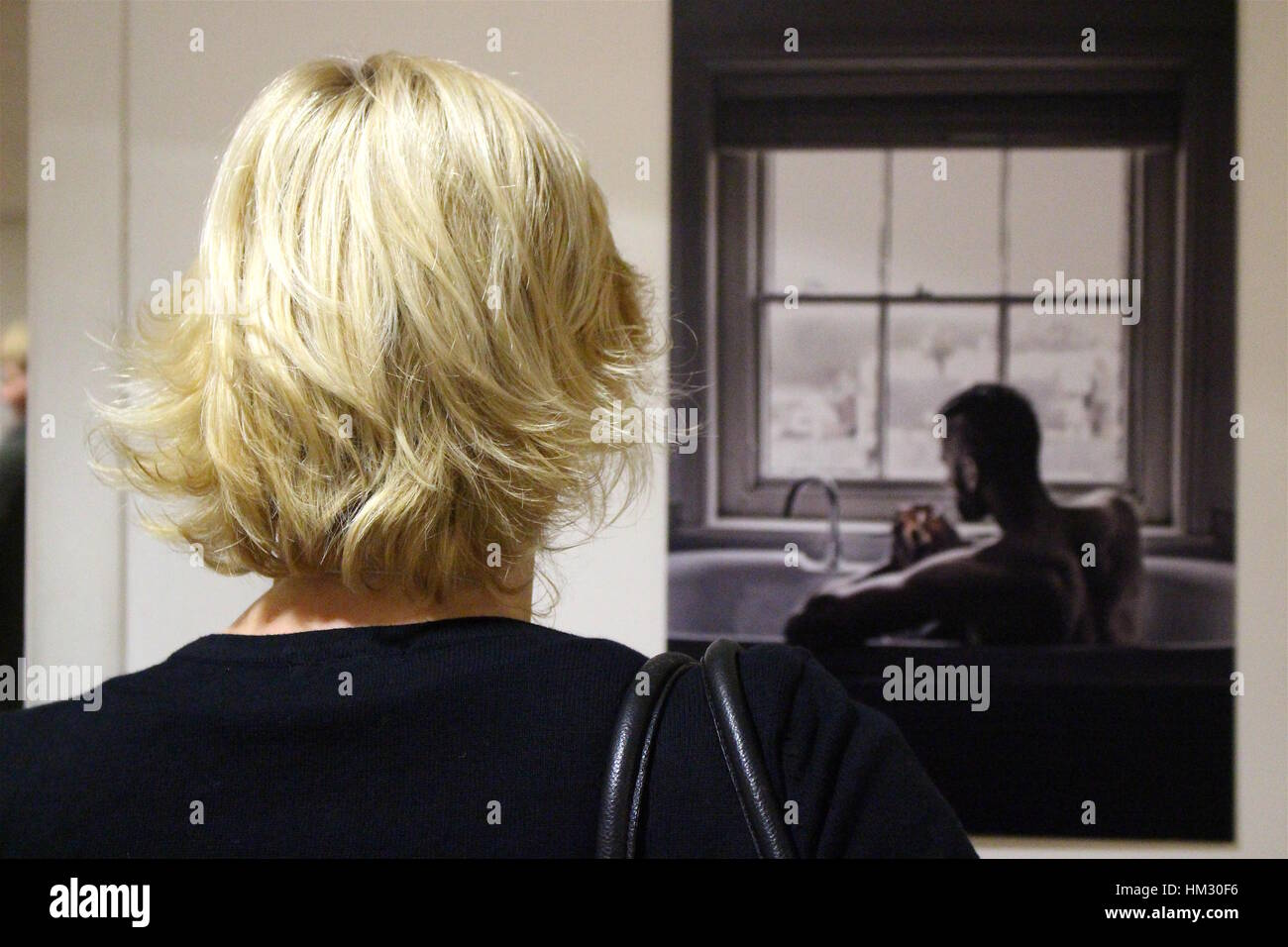 Short haired blond woman looking at the winning picture at London Photo Festival in Borough, London. May 2016 - Stock Image