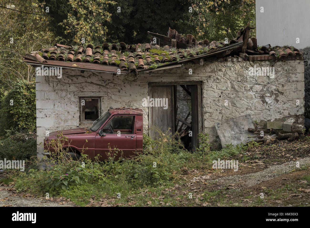 Derelict cottage with half a car outside; Meteora, Greece - Stock Image