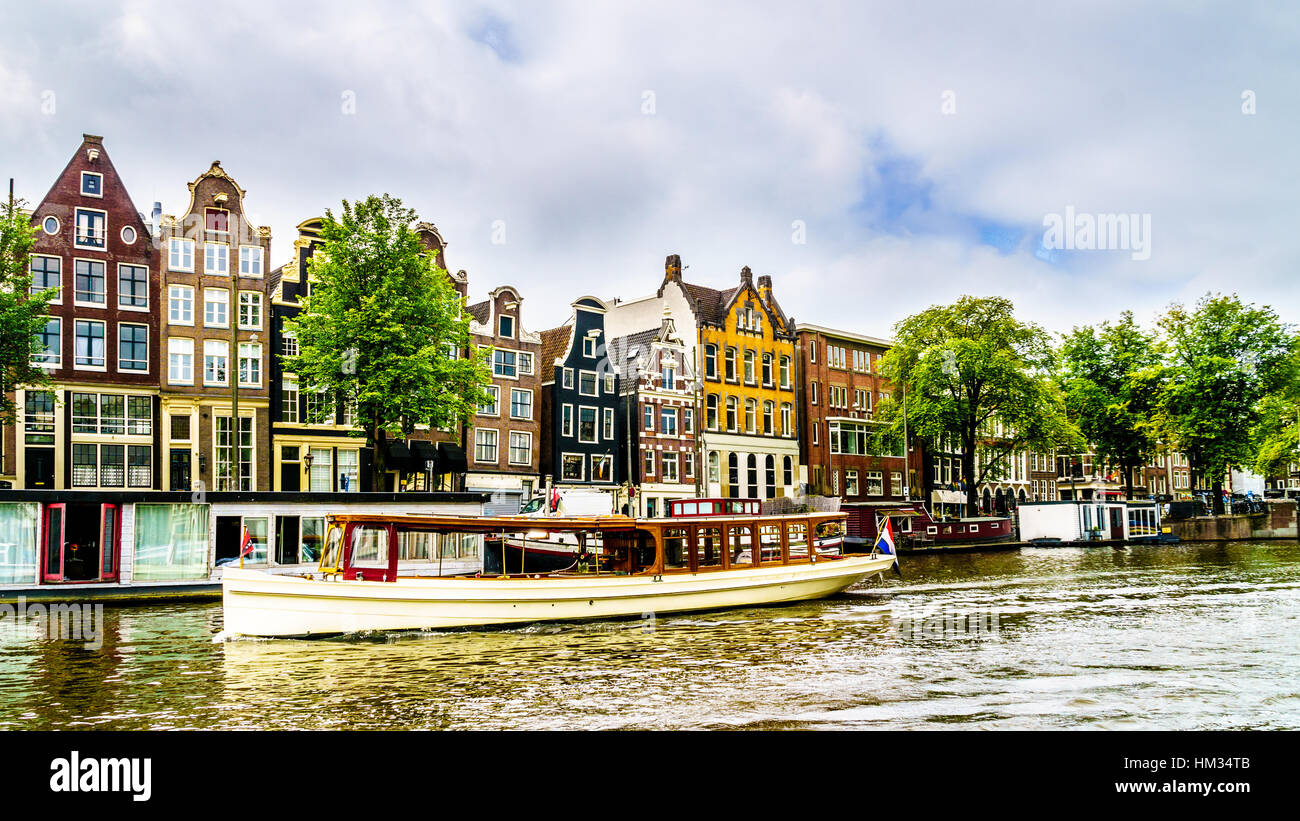Historic Buildings with Ornate Gables along the canals in old city of Amsterdam in the Netherlands Stock Photo