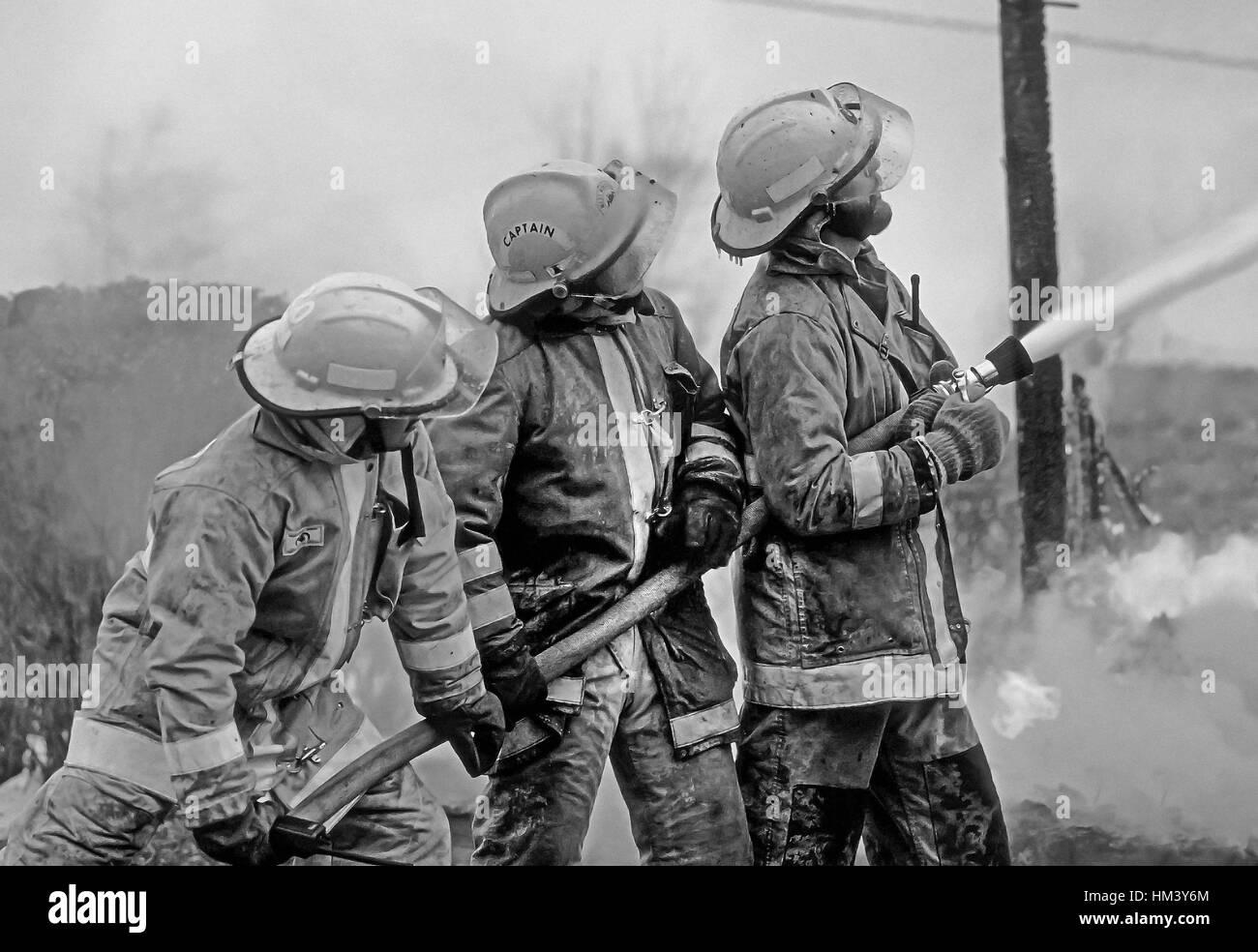 Three firefighters battle a blaze. - Stock Image