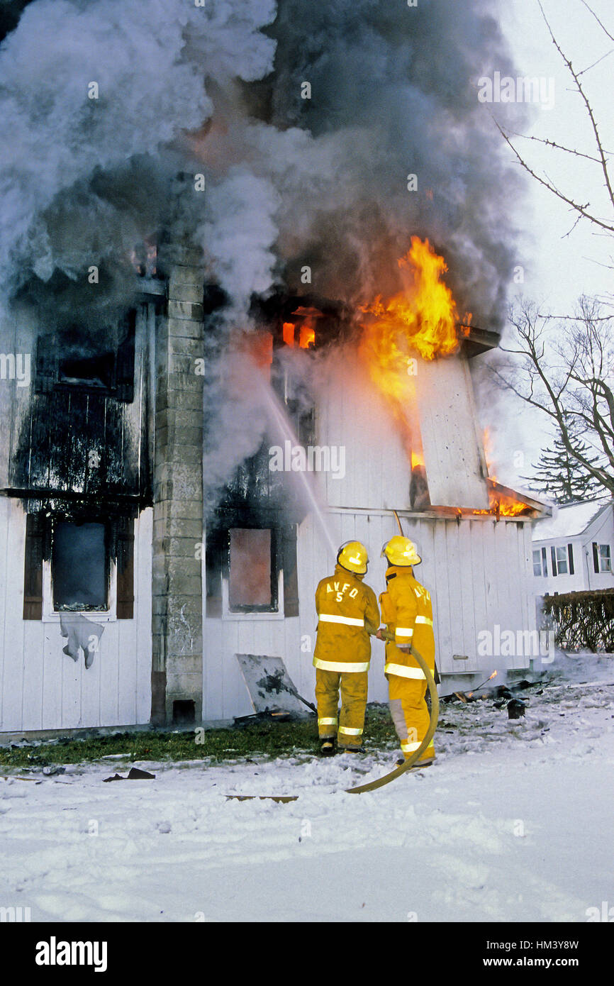 Two firemen battle a house fire in Ascutney, VT, USA. Digital slide scan. - Stock Image