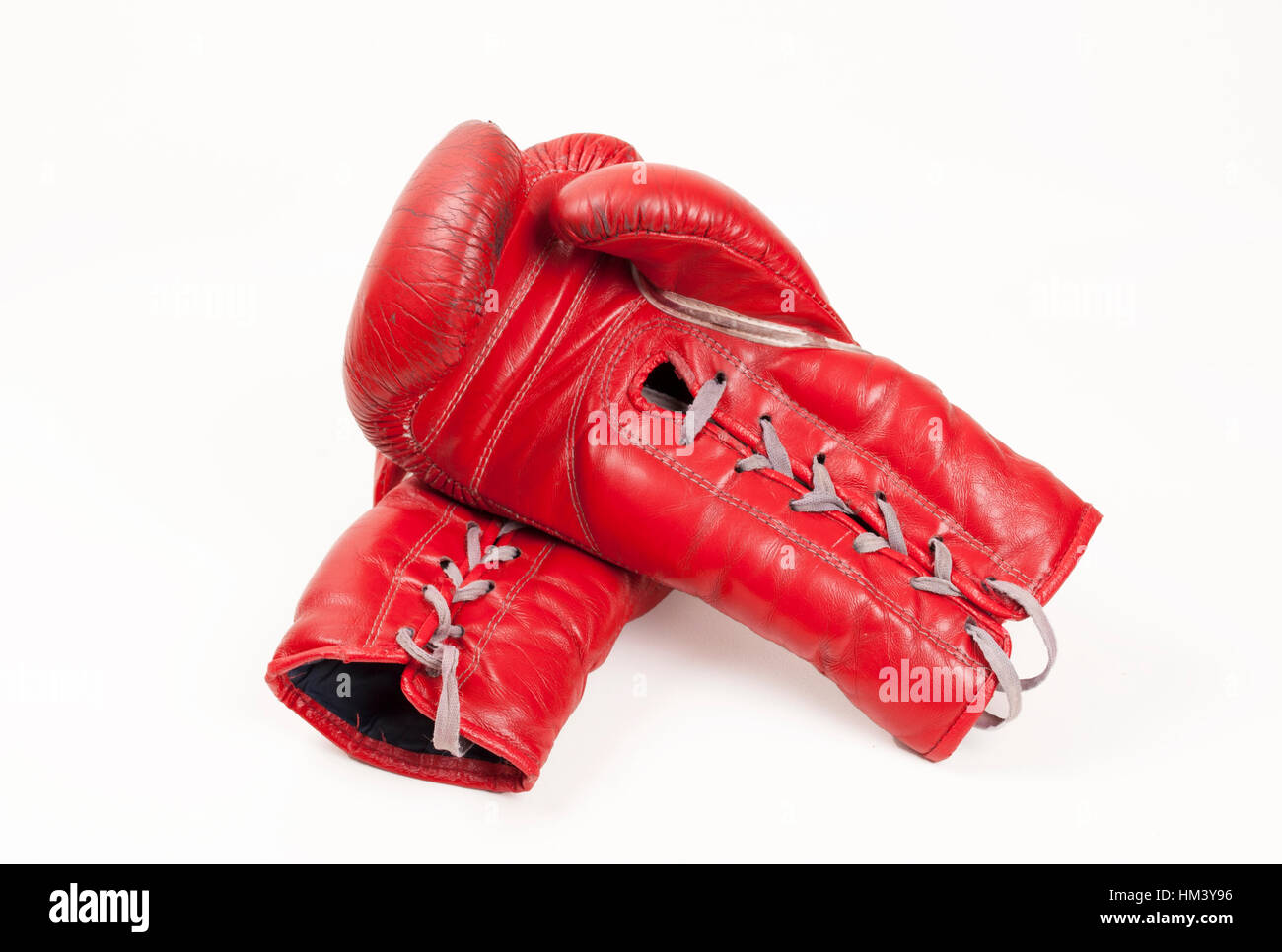 old used red leather boxing gloves putting hands together, isolated on white background Stock Photo