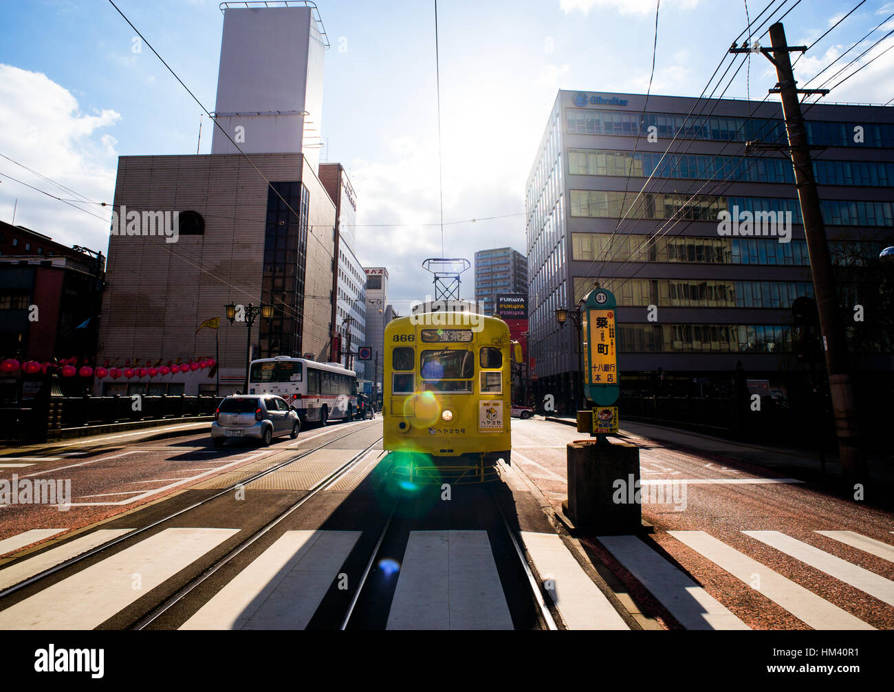 front view of a yellow vintage tram waiting at a zebra crossing in Nagasaki, Japan Stock Photo
