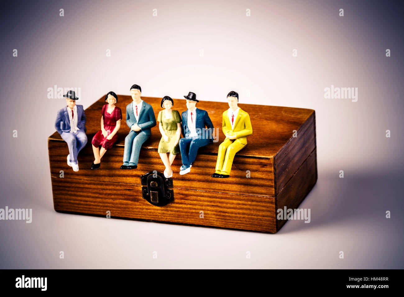 toy models of people sitting on the wooden box on white - Stock Image