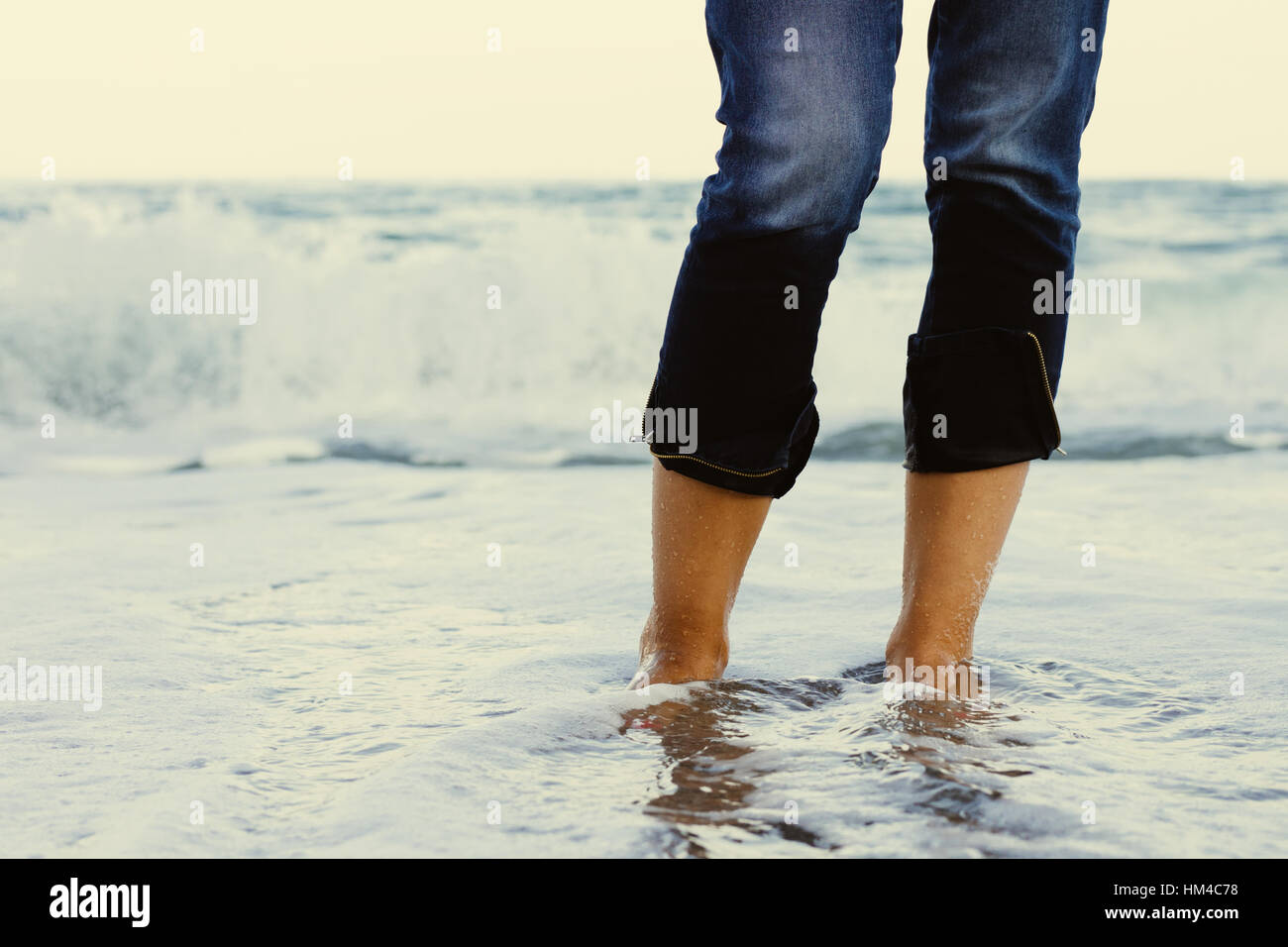 Female legs in jeans standing in the sea water on the background of a breaking wave. Stock Photo