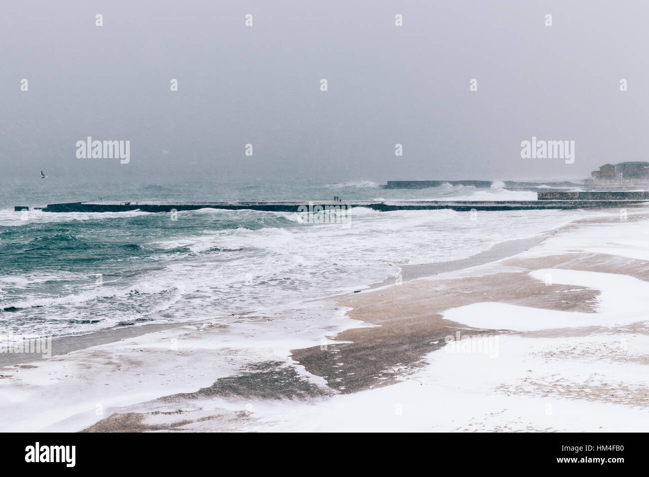 View of snow-covered pier and the sea during a snowfall in winter, soft focus Stock Photo