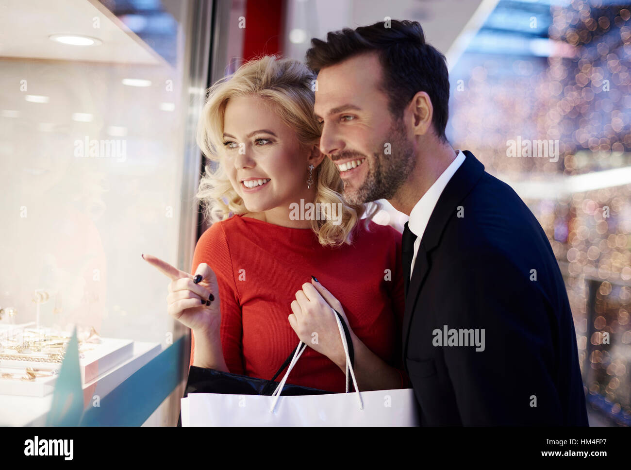 Couple looking through the stores window - Stock Image