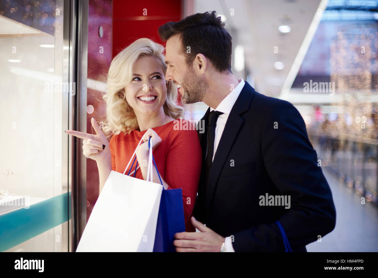 Two adults gazing at window shop - Stock Image
