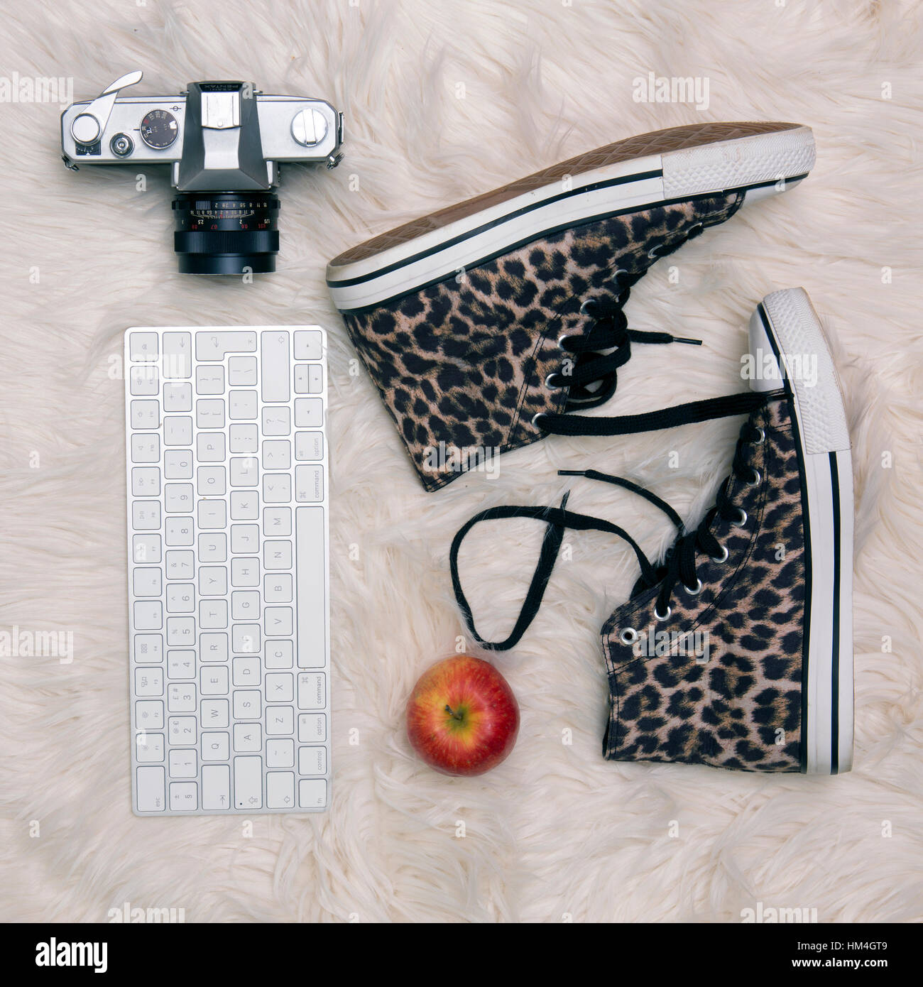 Lifestyle Flat Lay with leopard print boots old camera keyboard and apple on a fur rug - Stock Image