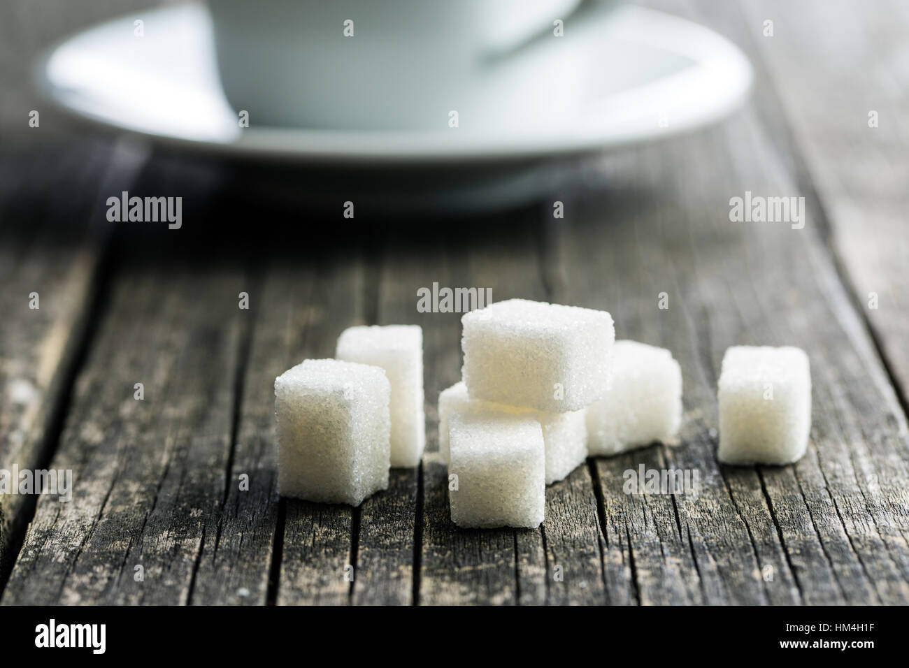 White sugar cubes on old wooden table. - Stock Image