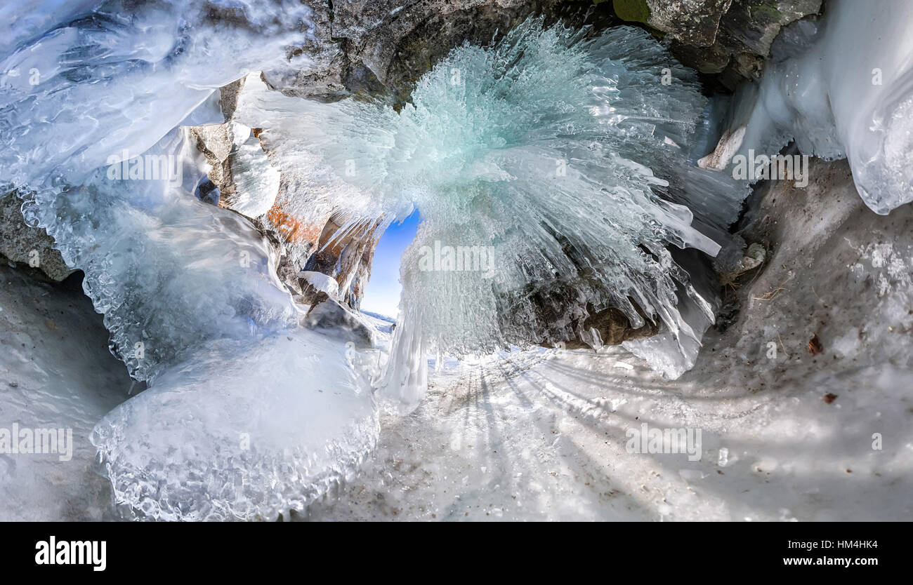 Panorama dawn in an ice cave with icicles on Baikal, Olkhon. - Stock Image