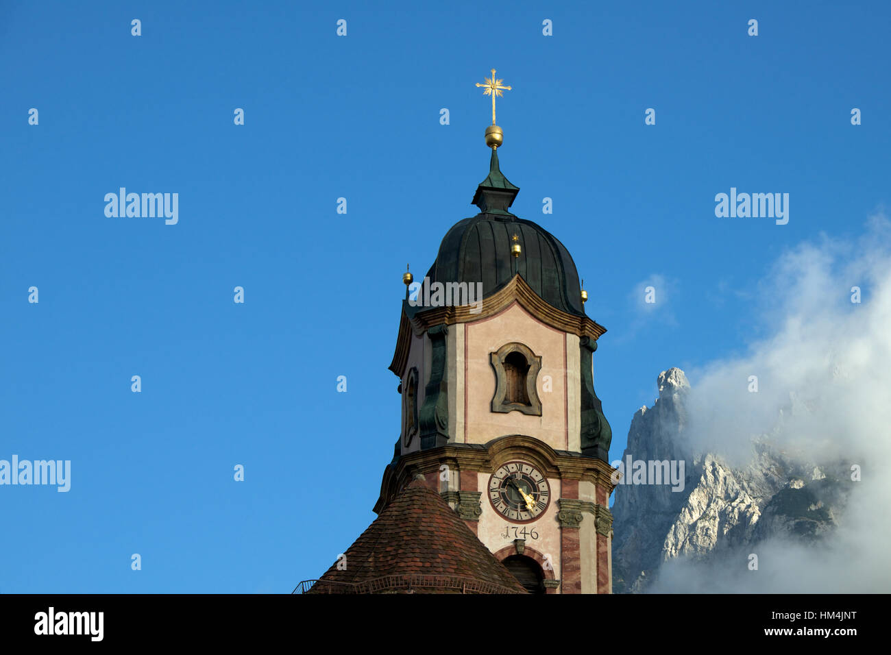 MIttenwald church tower and Karwendel mountains in the background, Bayern, Germany - Stock Image