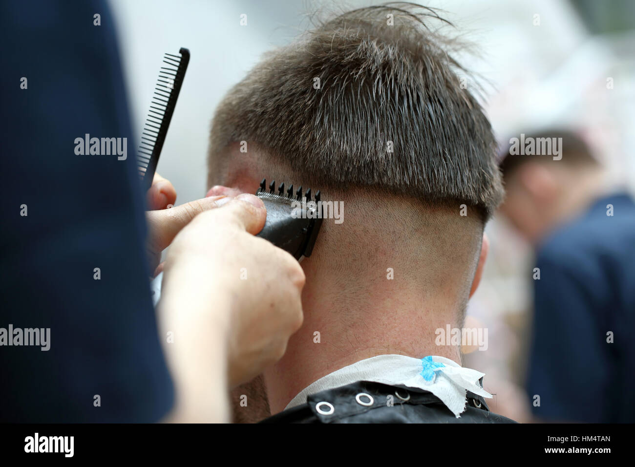 Barber shaving hair by electric trimmer - Stock Image