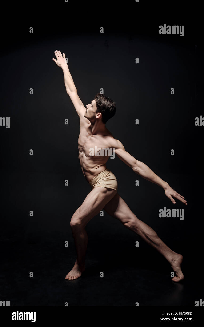 Enthusiastic young dancer stretching in the black studio - Stock Image