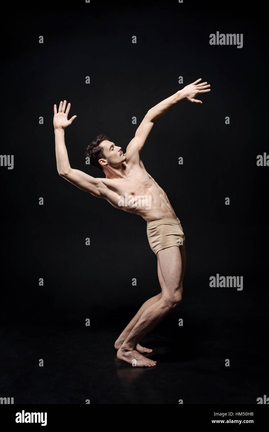Inspired young ballet dancer moving in the studio - Stock Image