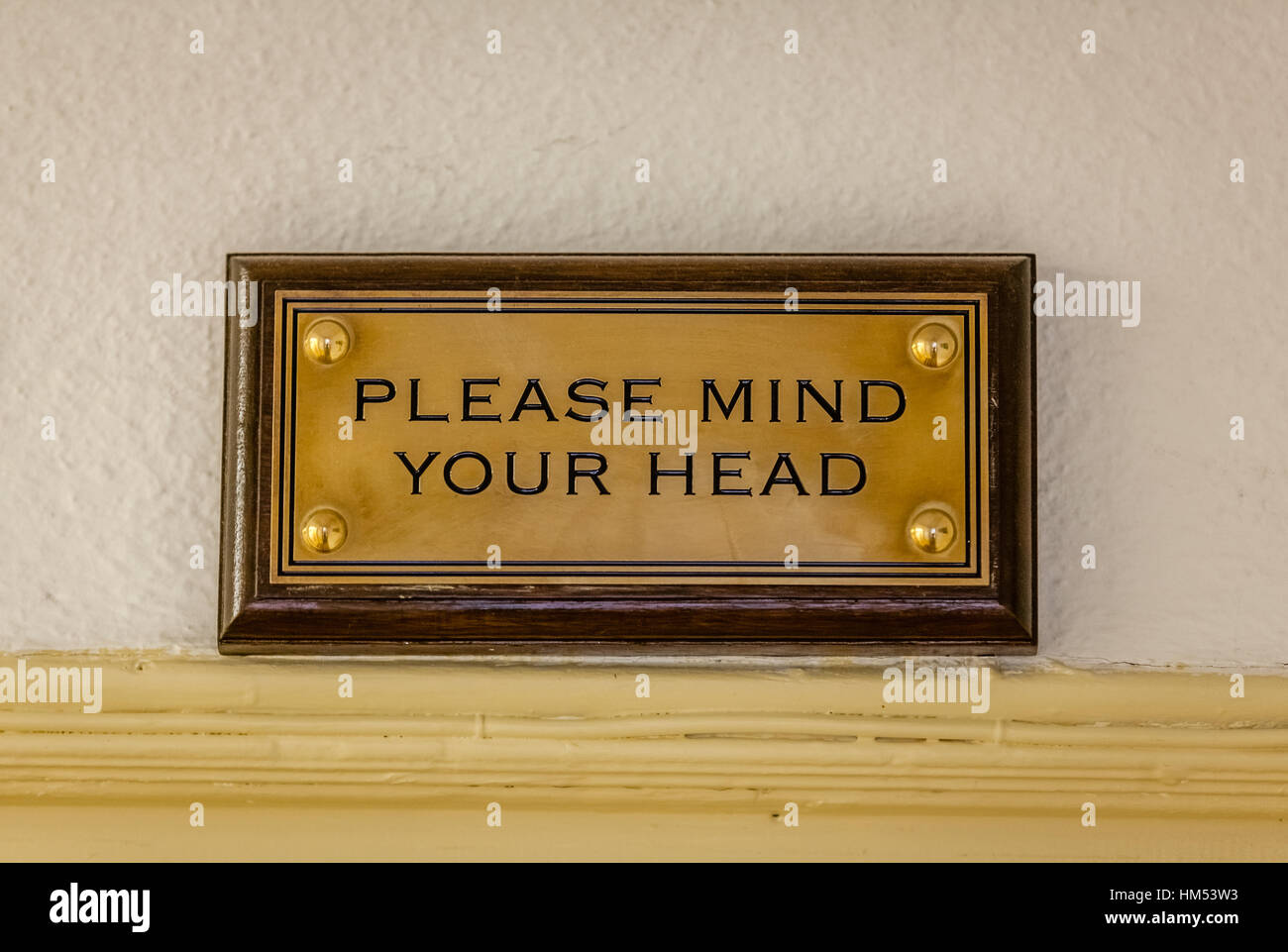Mind your head plaque in a building with small doors - Stock Image