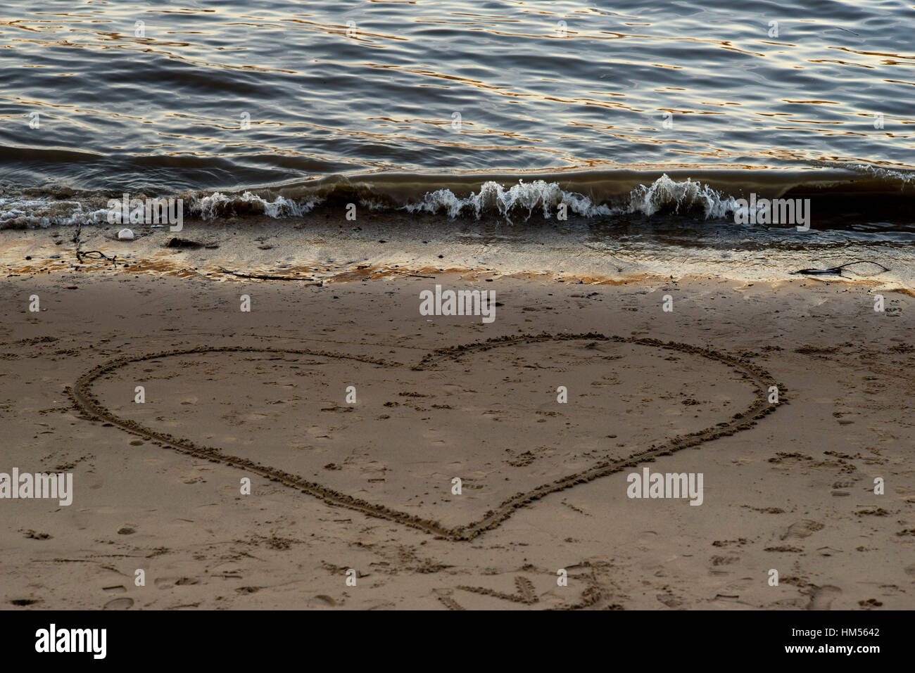 Heart shape drawn in the sand on a beach. London, Great Britain - Stock Image