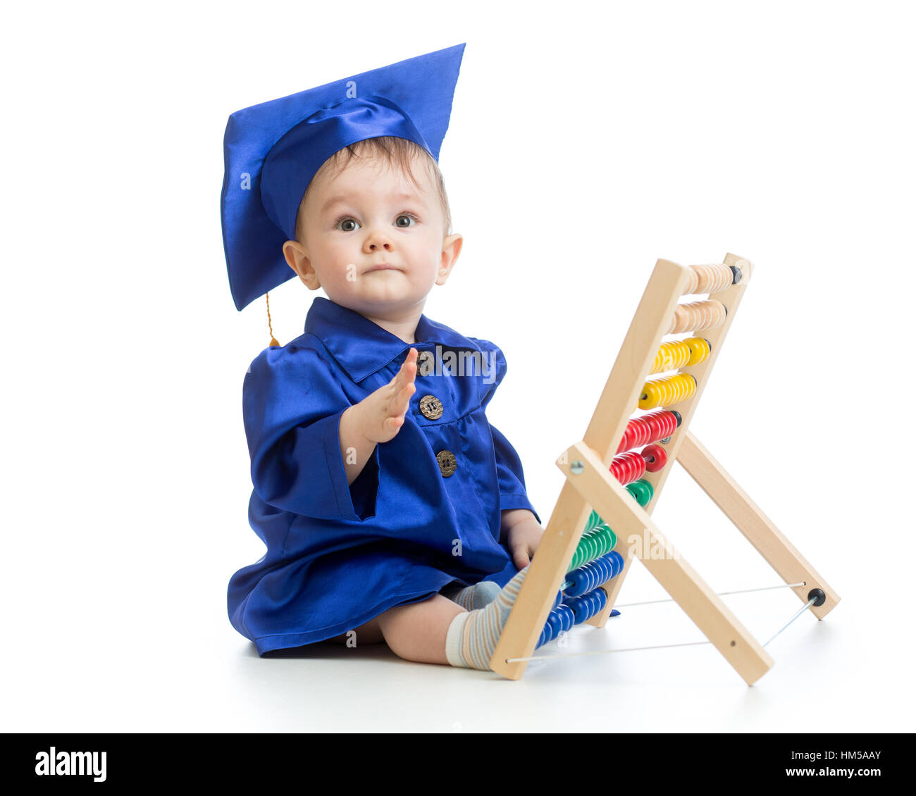 Child dressed in academic clothes with counter. Early kids education. - Stock Image