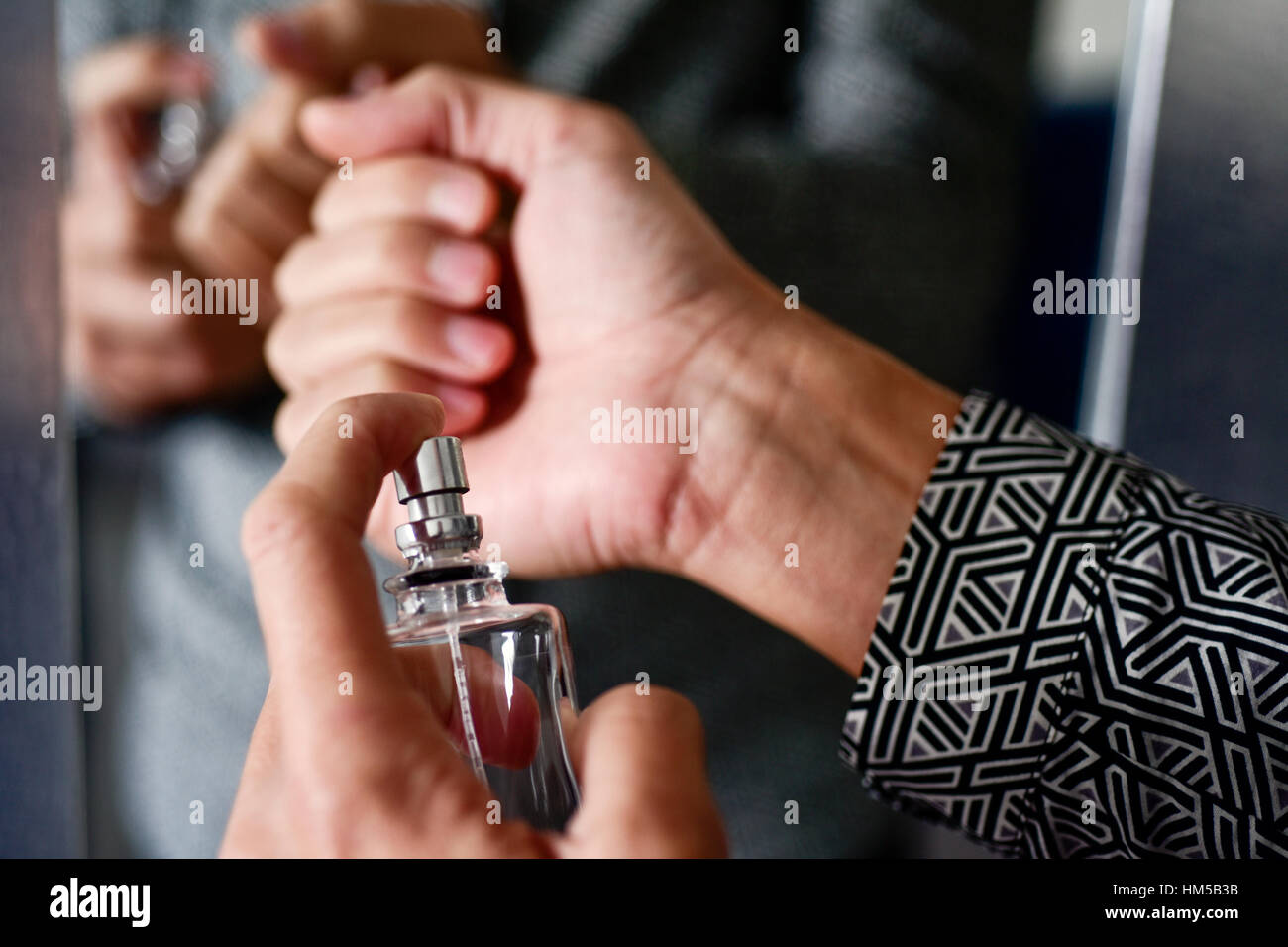 closeup of a young caucasian man spraying perfume on his wrists - Stock Image